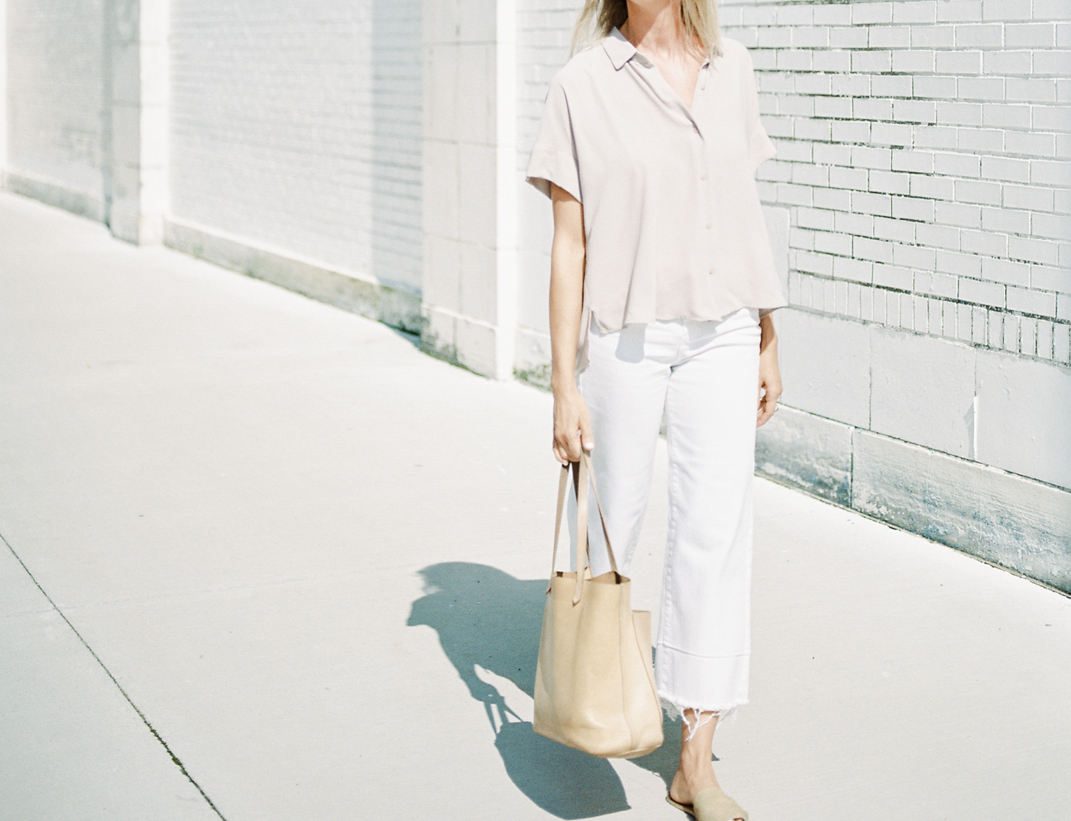 A Detroit female entrepreneur and brand designer carries a Madewell bag and walks downtown during her brand photos