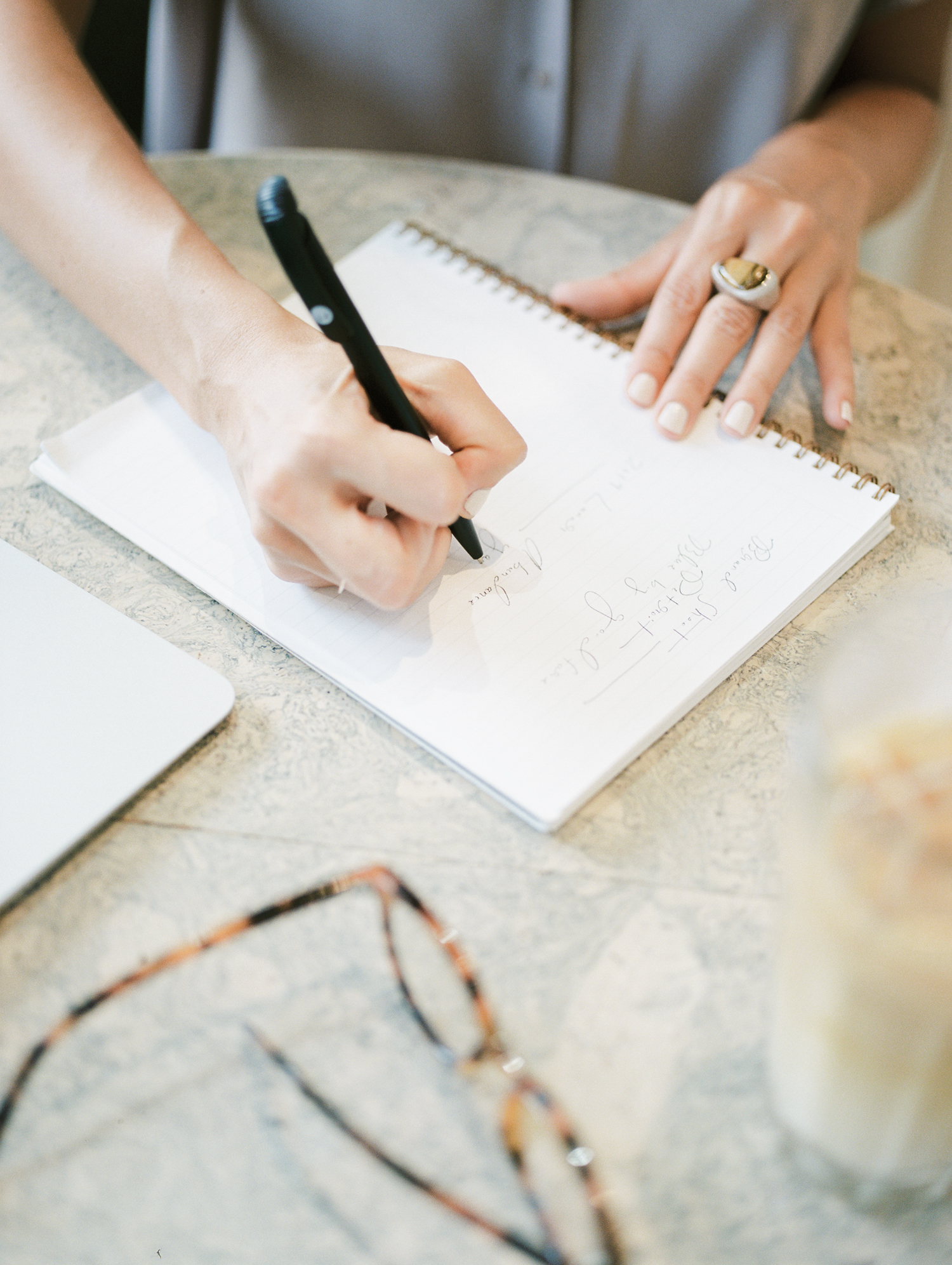 A female business owner and designer writes in a notebook at a Detroit coffee shop during her film brand photoshoot