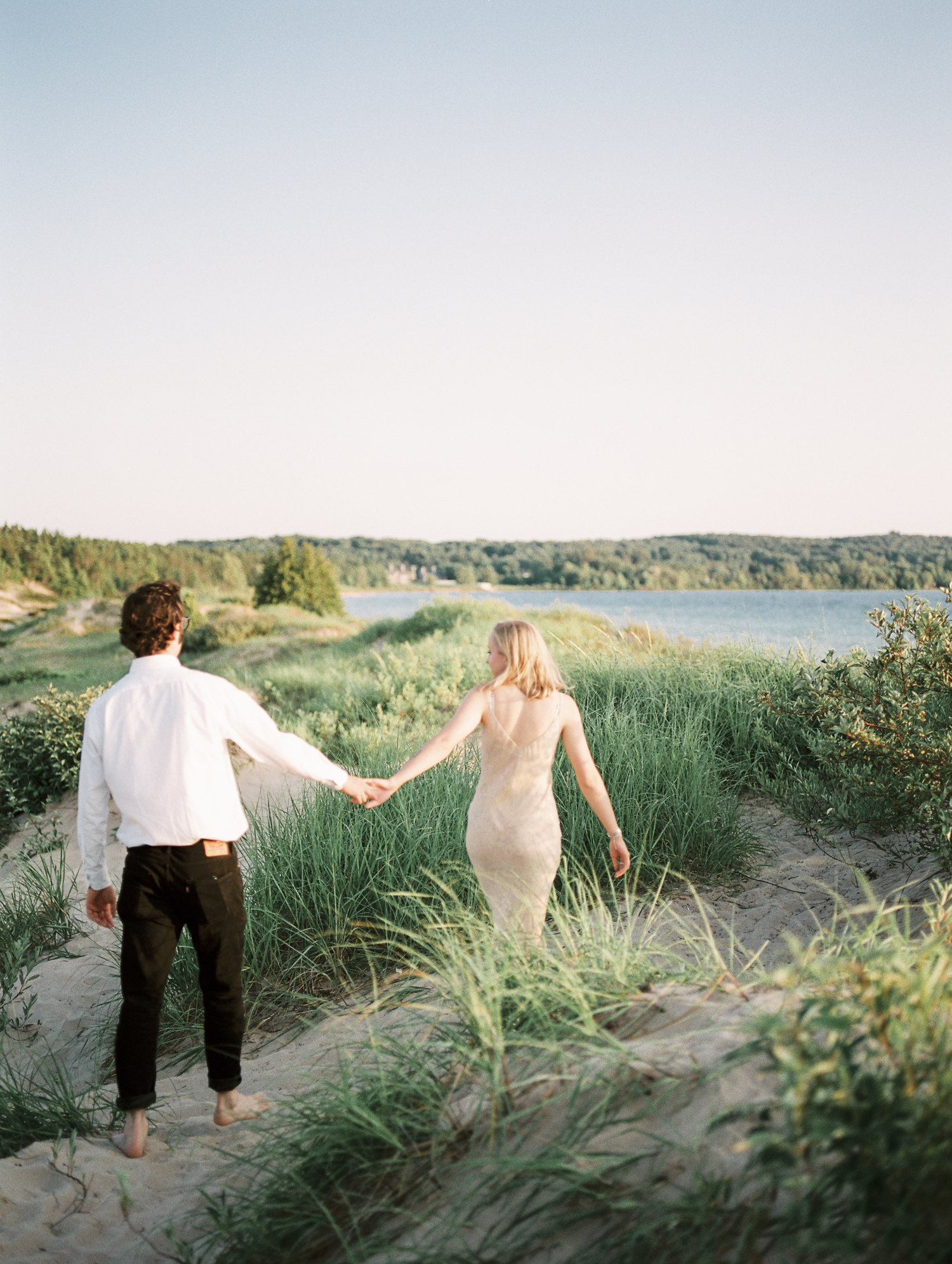A couple explores beautiful sand dunes on Lake Michigan during their engagement photos in Petoskey