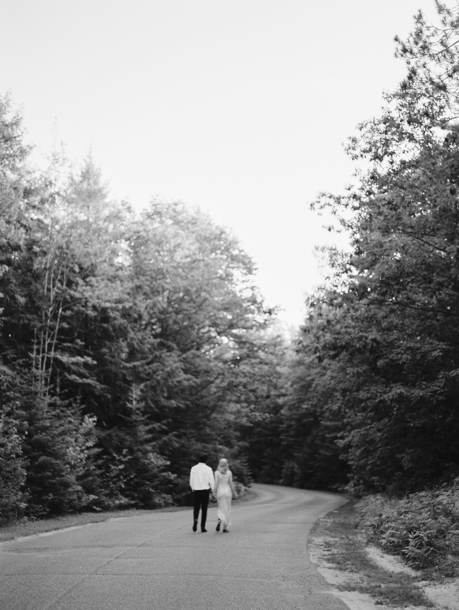 A couple holds hands and walks a winding path at Petoskey State park during their Michigan engagement photo session