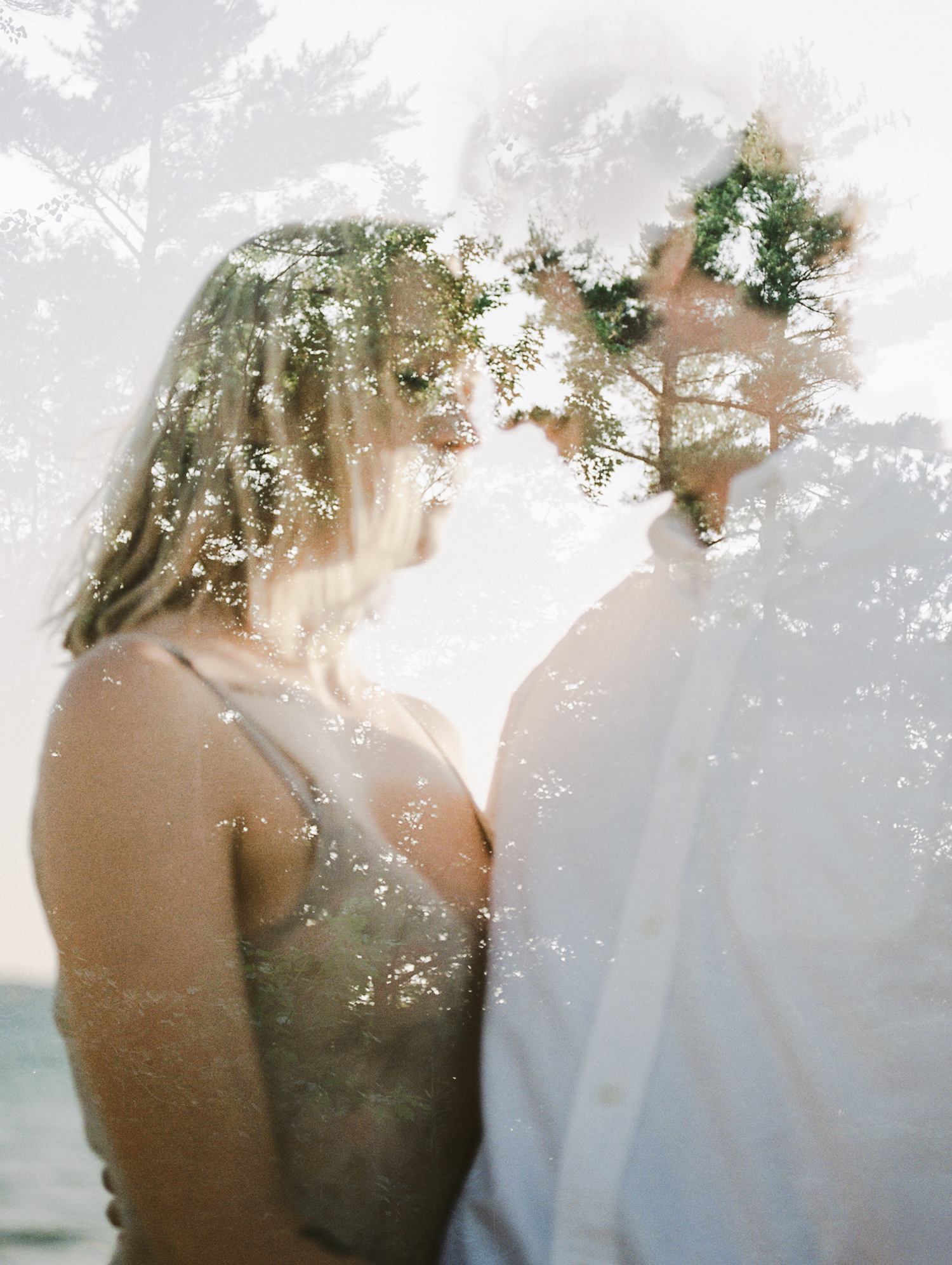 A film double exposure of a couple embracing on a Lake Michigan beach during their Northern Michigan engagement photos in Petoskey