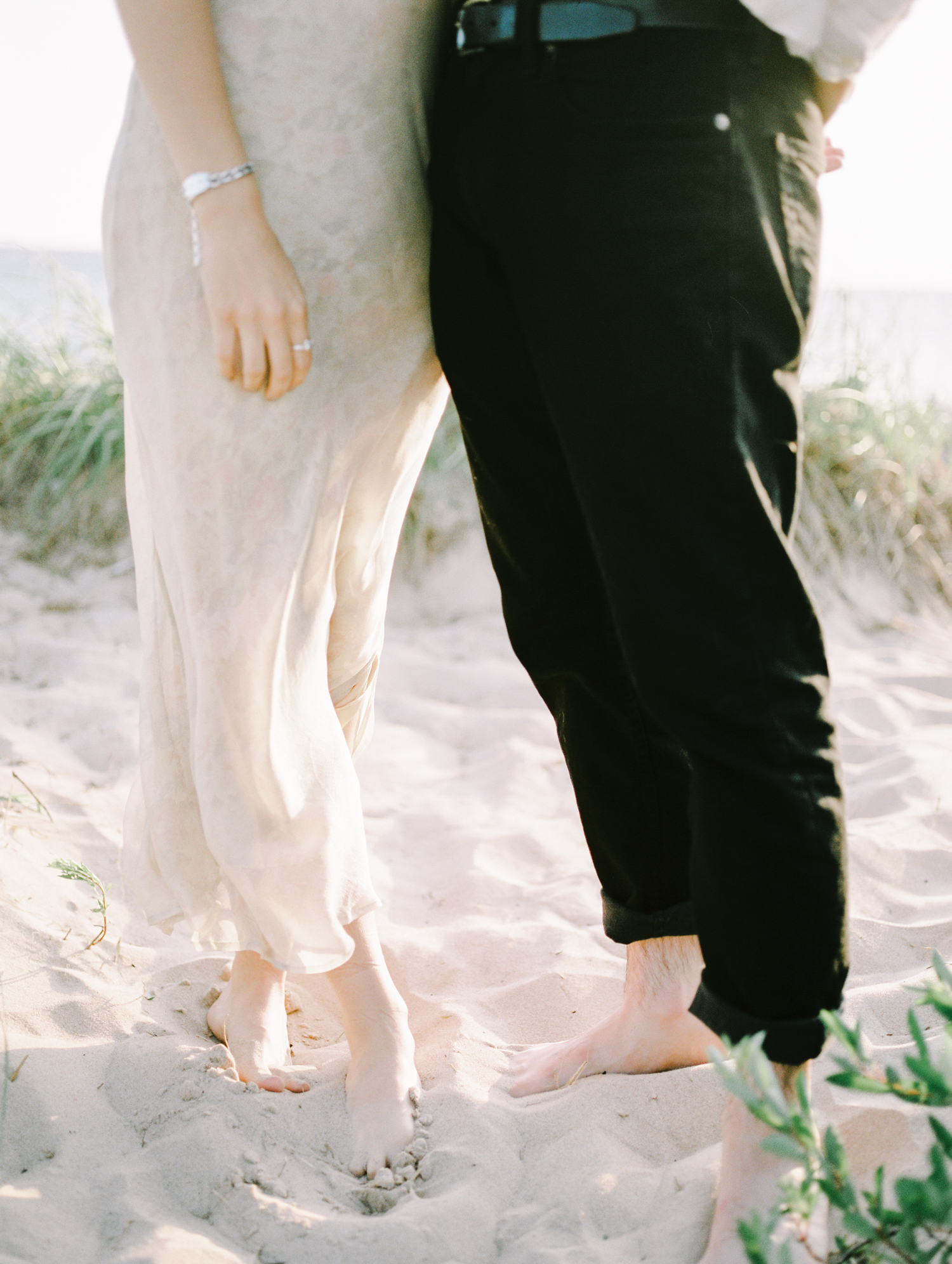 A couple stands with their feet in the sand on a Lake Michigan beach