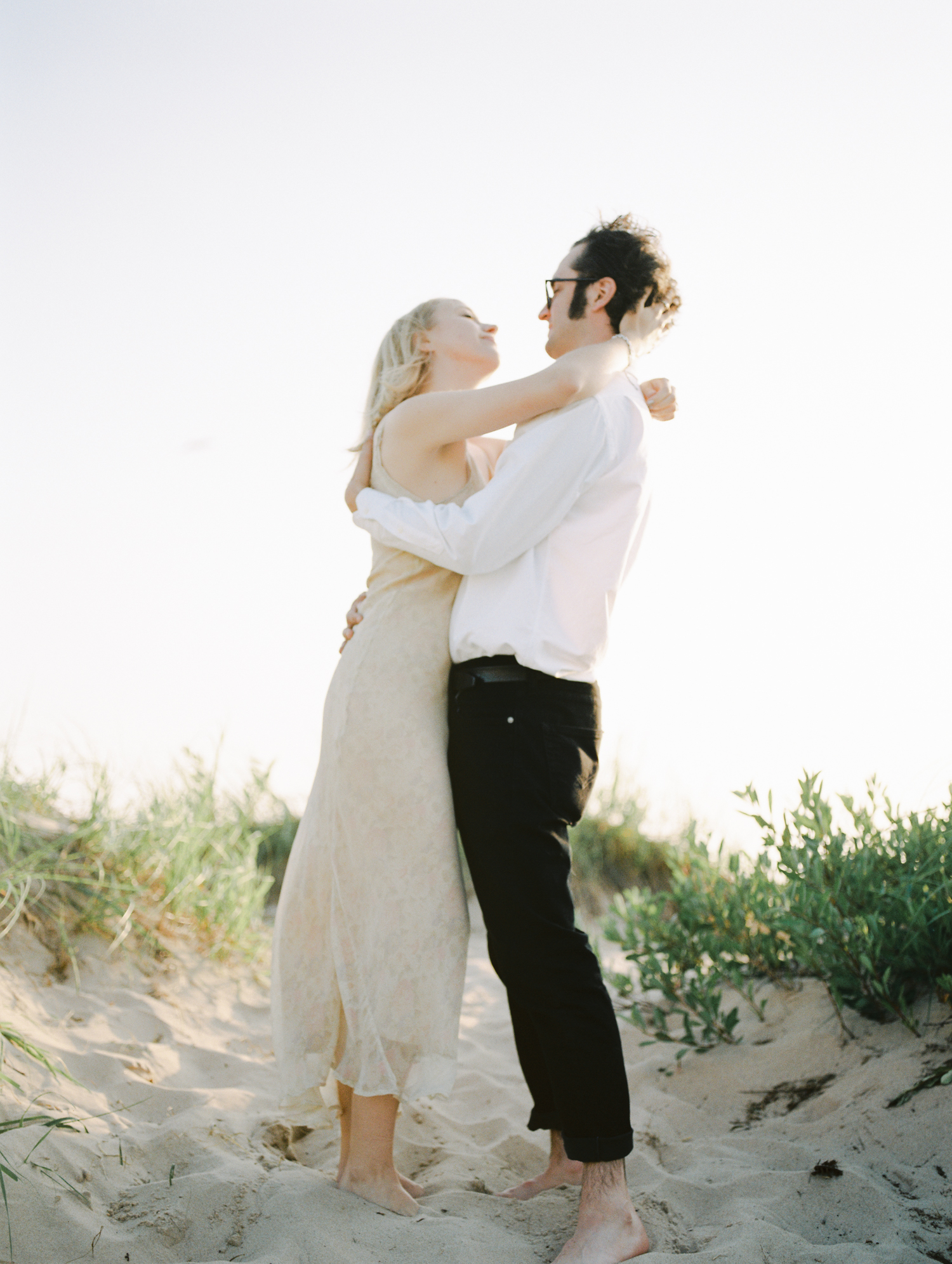 A couple embraces on beautiful sand dunes on Lake Michigan during their engagement photos in Northern Michigan
