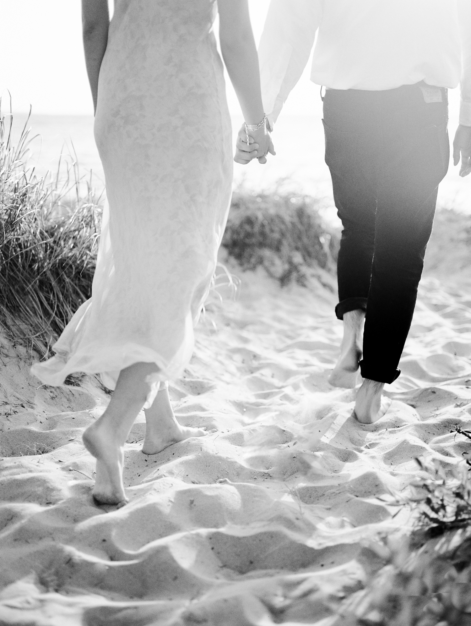 A couple holds hands and walks through beautiful sand dunes on Lake Michigan during their Petoskey engagement photos