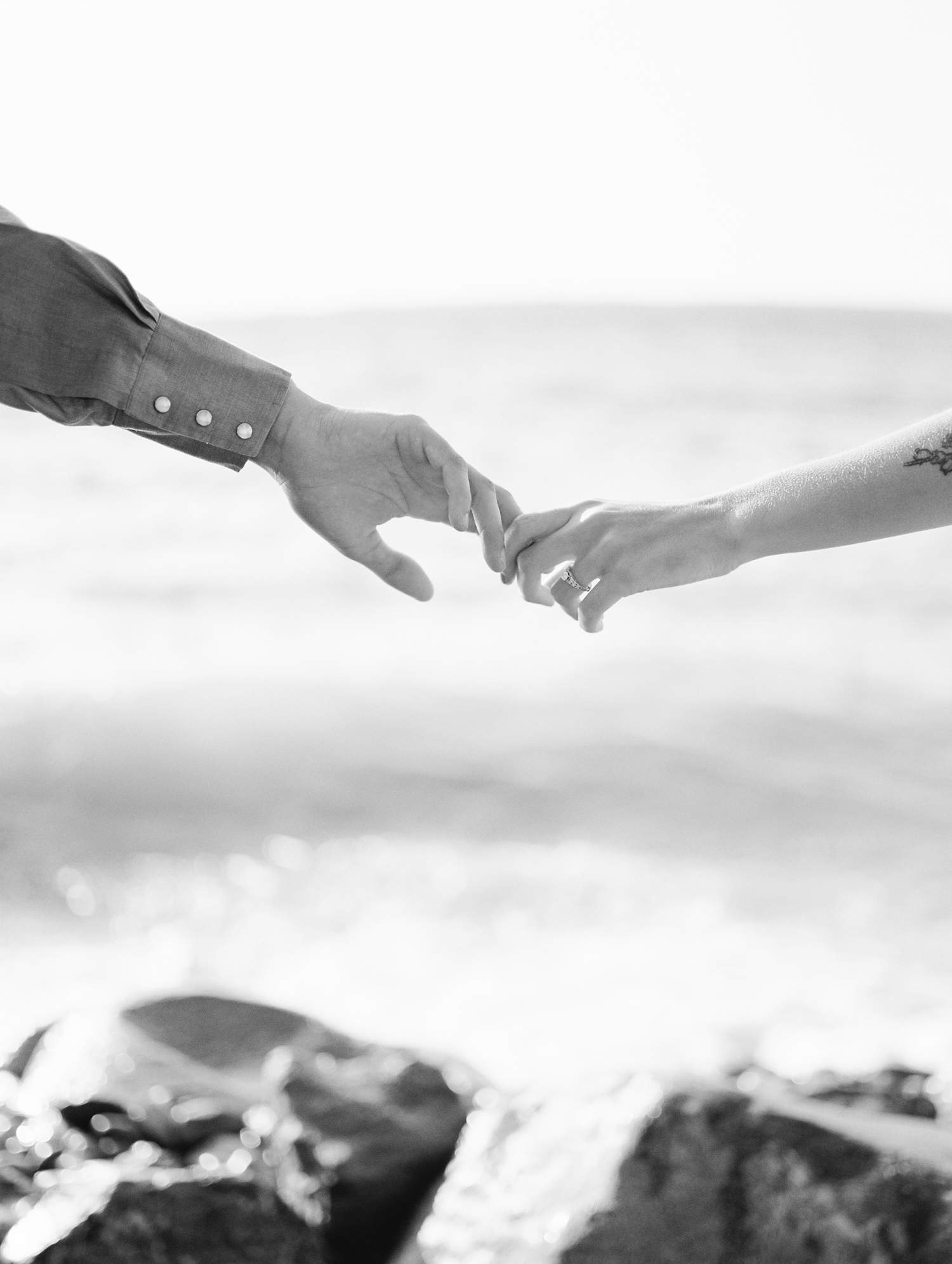A couple's hands reaching for each other in front of Lake Michigan during their Northern Michigan engagement photos