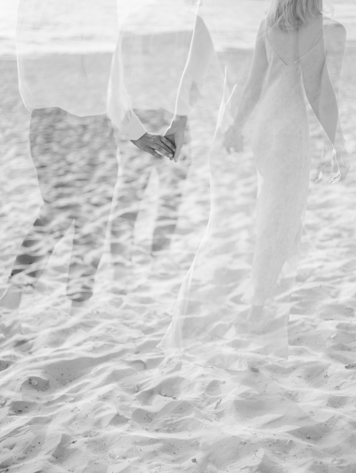 A film double exposure shows a couple walking along a Lake Michigan beach in Petoskey, Northern Michigan during their engagement photos