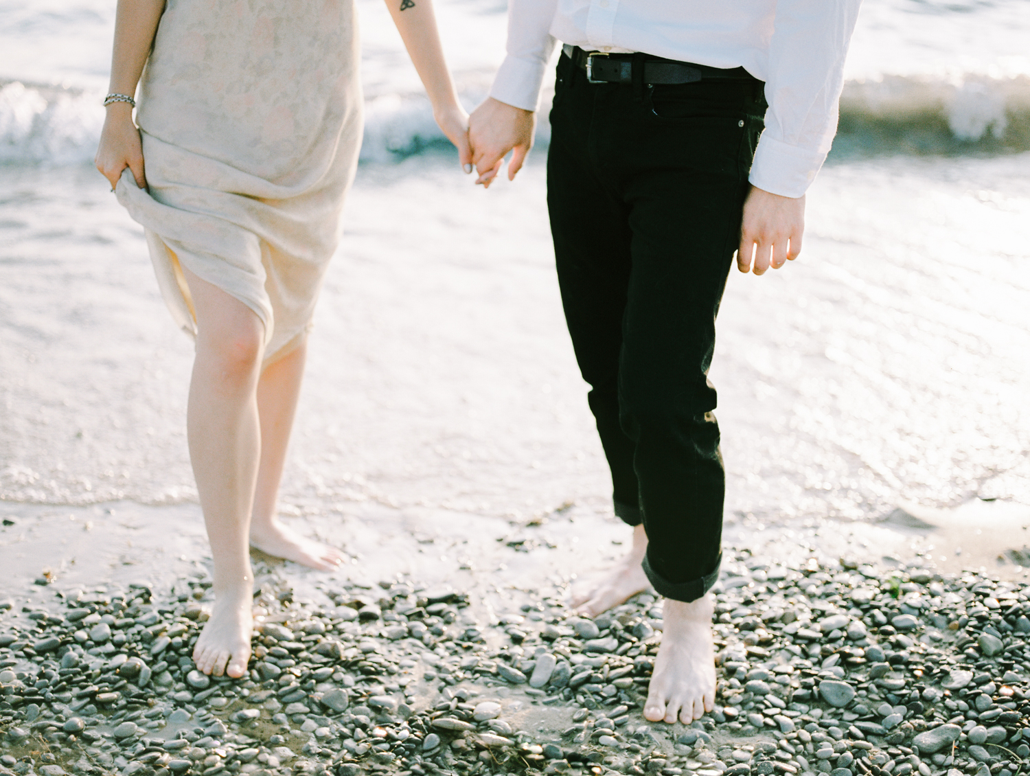 A light and airy film photo of a couple holding hands and standing on a rocky Lake Michigan beach