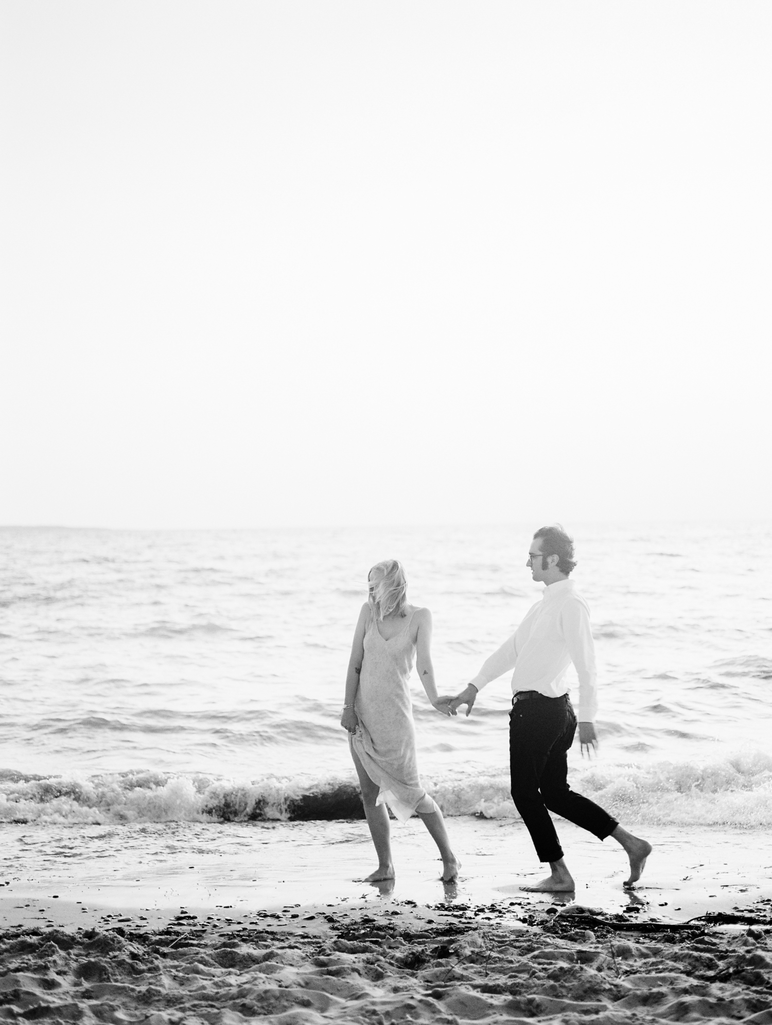 A couple walks along Lake Michigan during their Petoskey sunset engagement photos