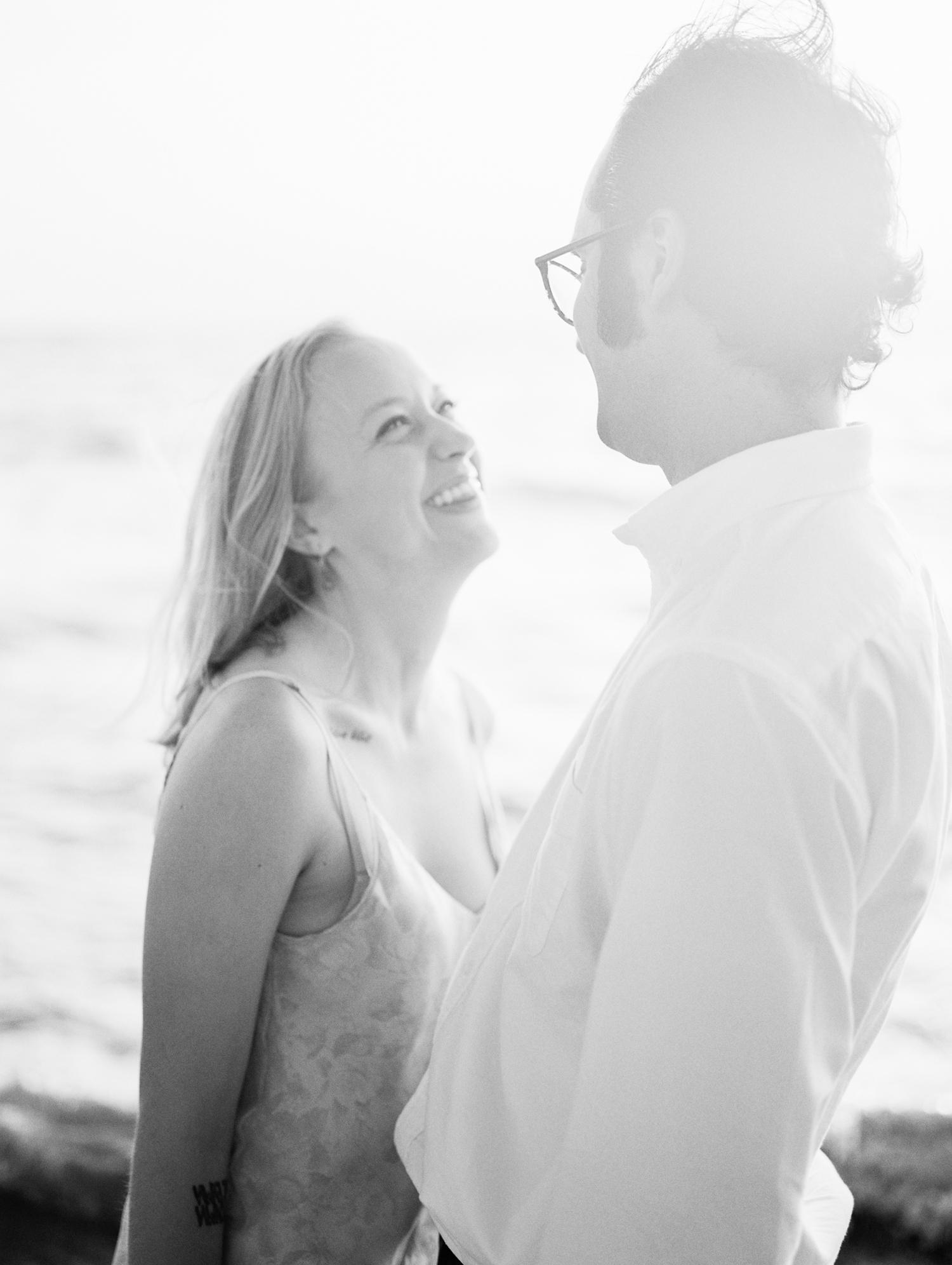 A light and airy film photo of a couple laughing together during their Petoskey engagement pictures