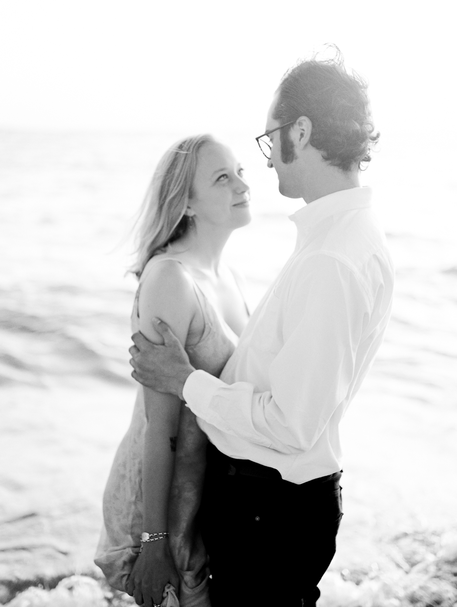 A woman looks at her man while they embrace on a Lake Michigan beach during their Petoskey engagement photos