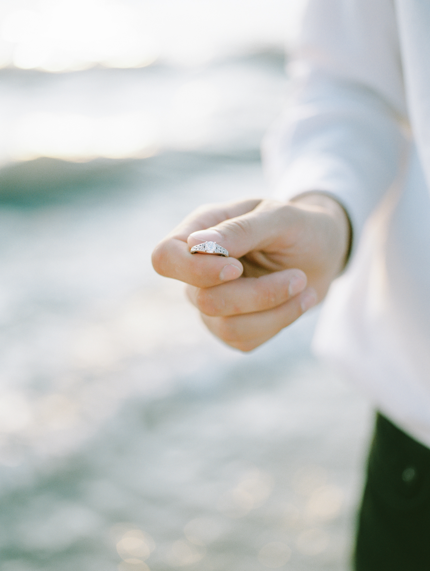 A man holds a white gold diamond engagement ring with vintage detail with Lake Michigan in the background for film engagement photos in Northern Michigan