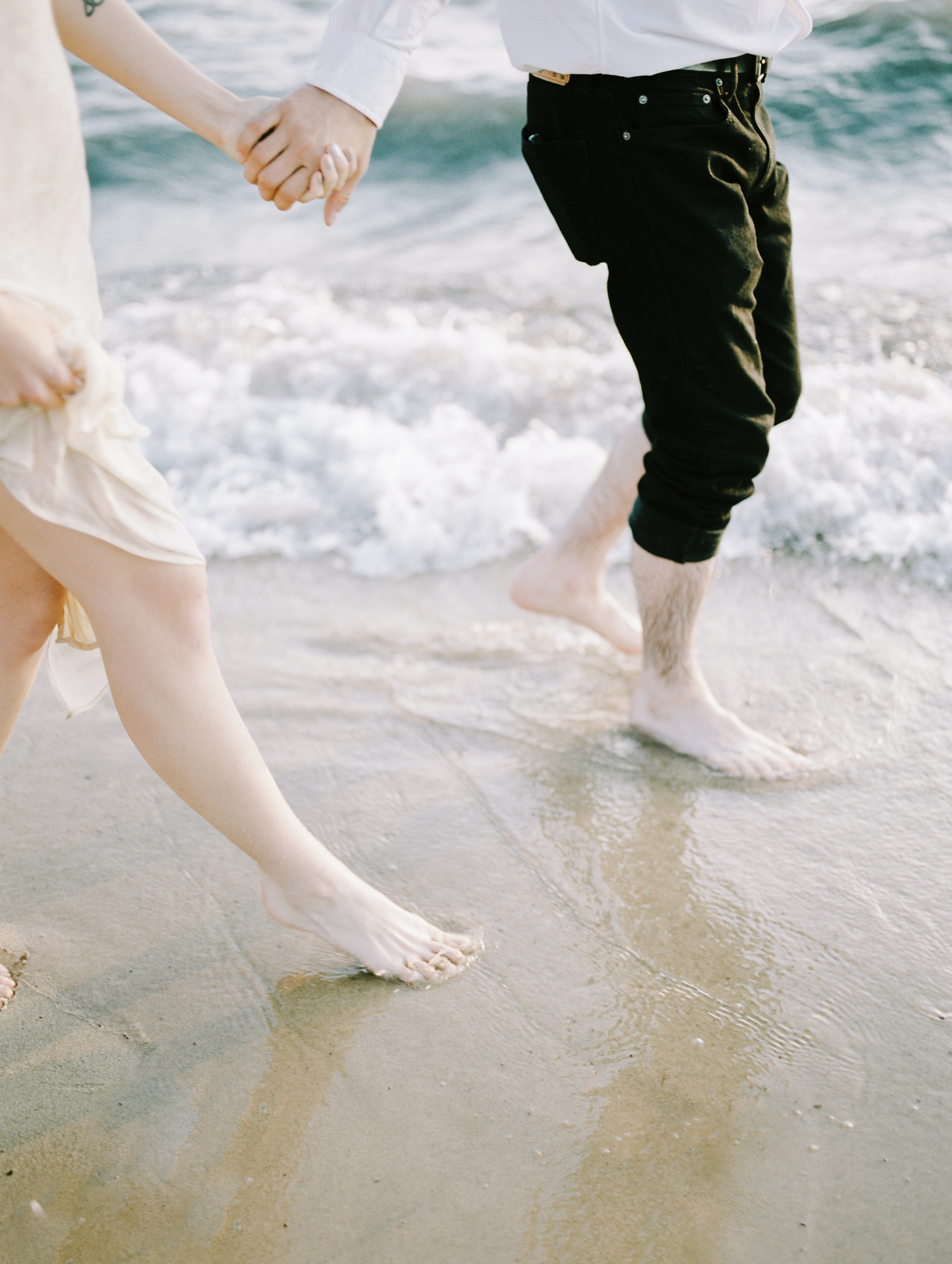 A couple's feet in the waves on a Lake Michigan beach while they walk hand-in-hand at their Petoskey engagement session