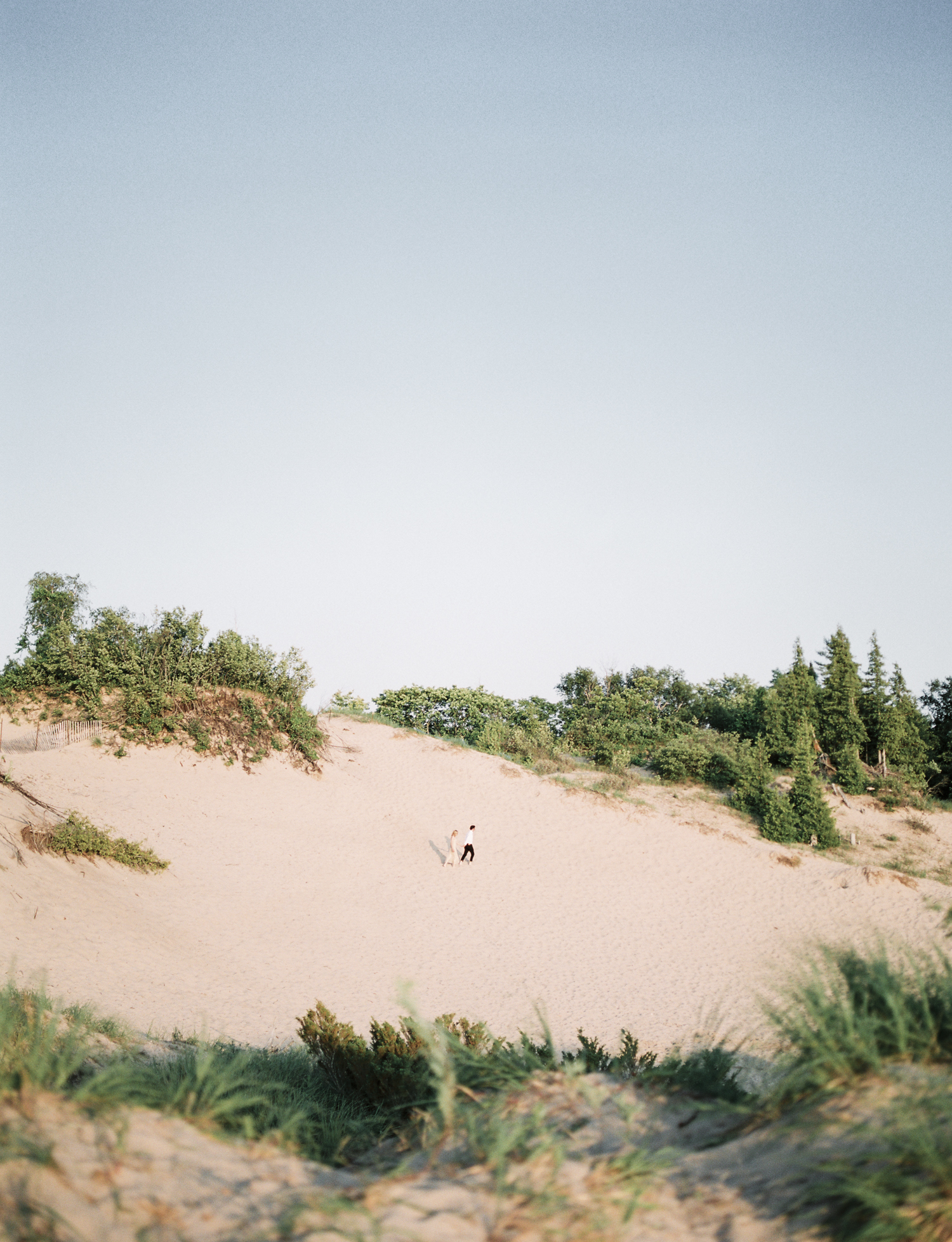 A couple is seen running across Lake Michigan sand dunes during their engagement photos in Petoskey