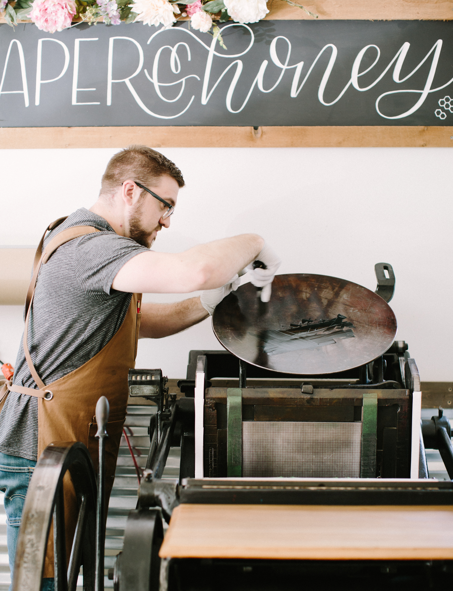 A pressman for Paper and Honey applies ink to an antique letterpress during brand photos in Brighton, Michigan
