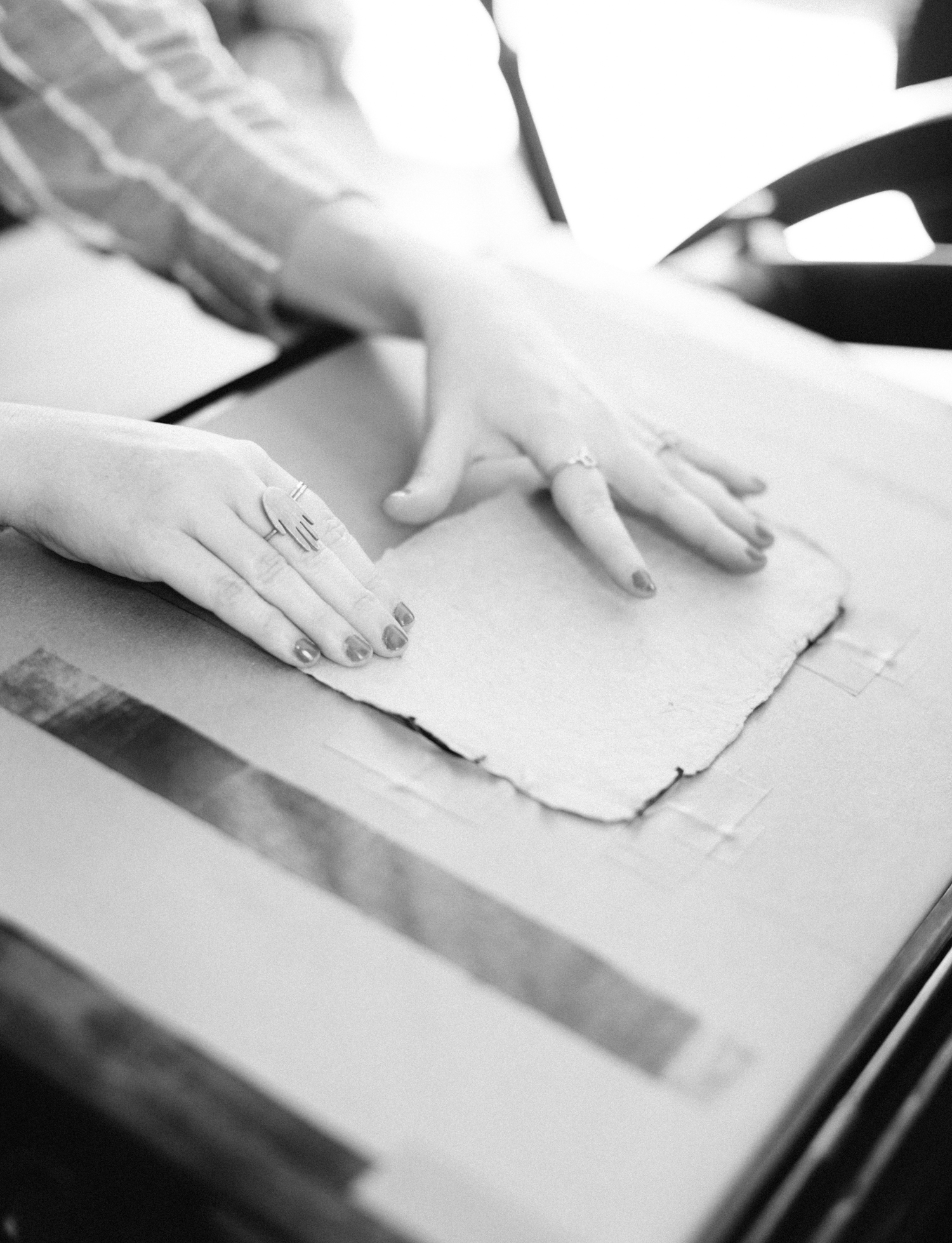 A designer's hands adjust paper on an antique letterpress in Brighton, Michigan during brand photography