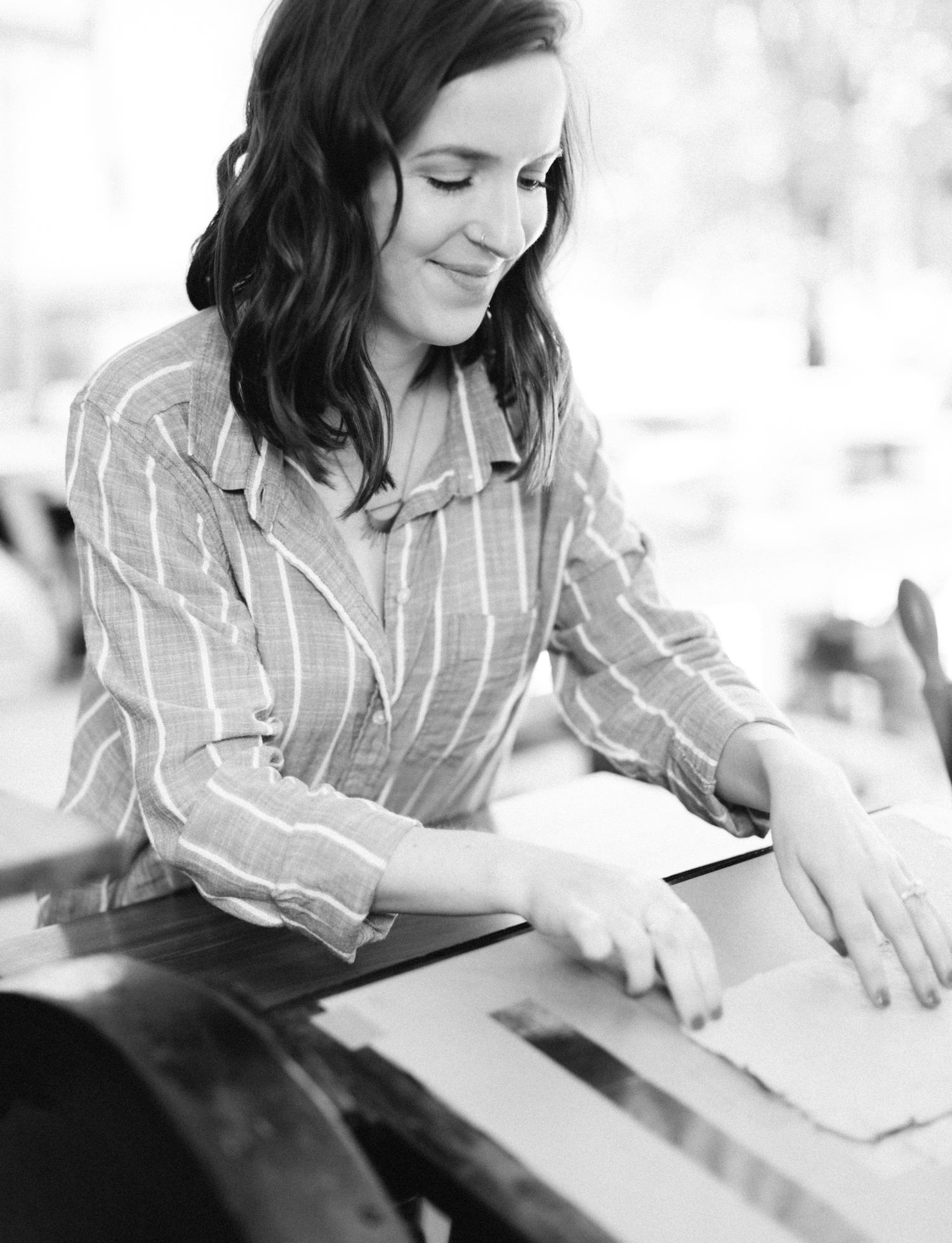 A designer and business owner adjusts paper on her antique letterpress during her brand photos in Detroit, Michigan
