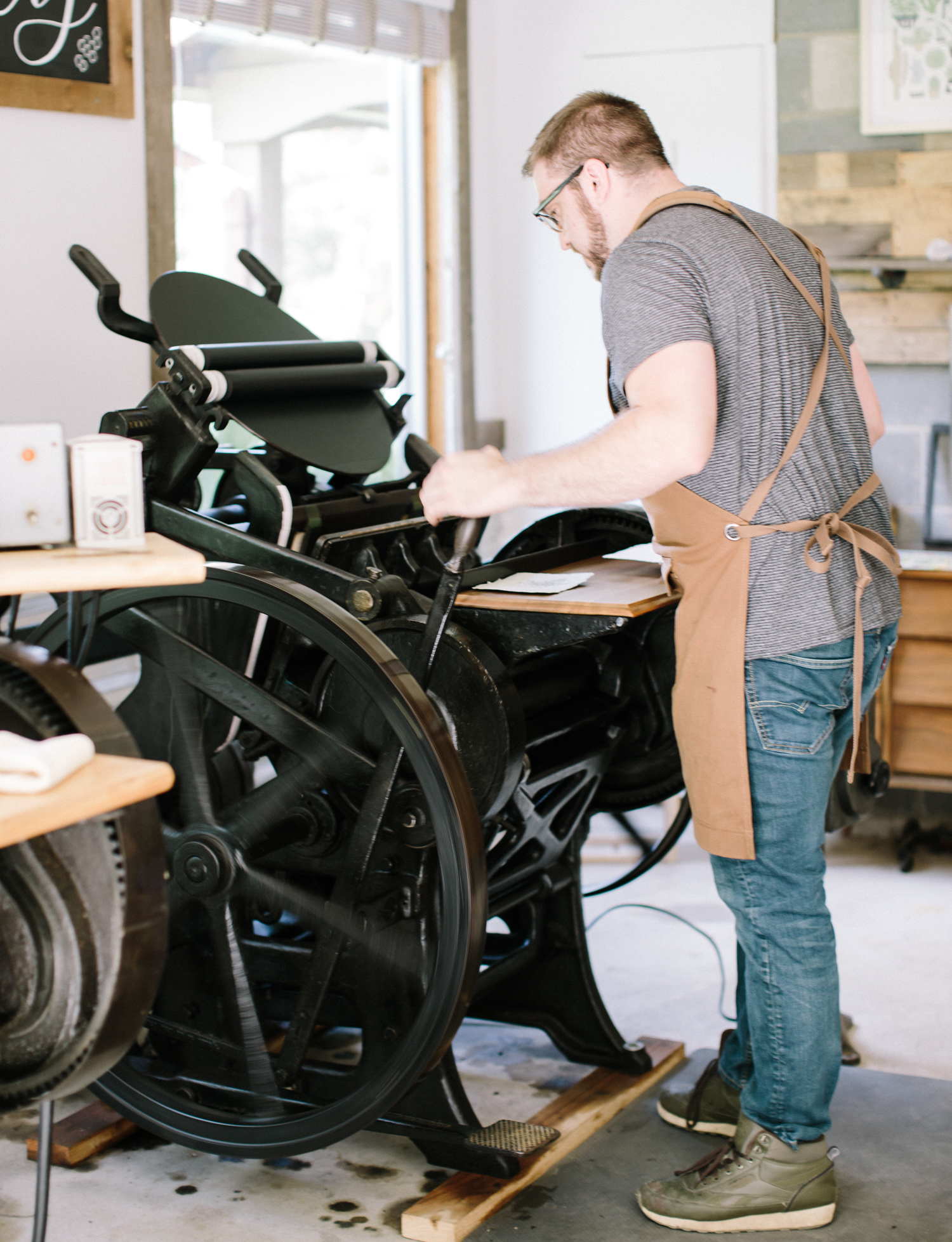 A pressman uses an antique letterpress during brand photography for Paper & Honey letterpress studio in Michigan