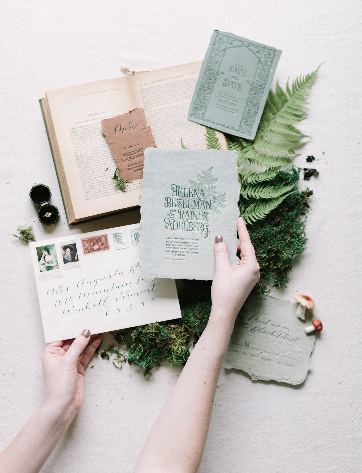 A designer places custom wedding invitations on handmade paper in a beautiful flat lay with moss and ferns