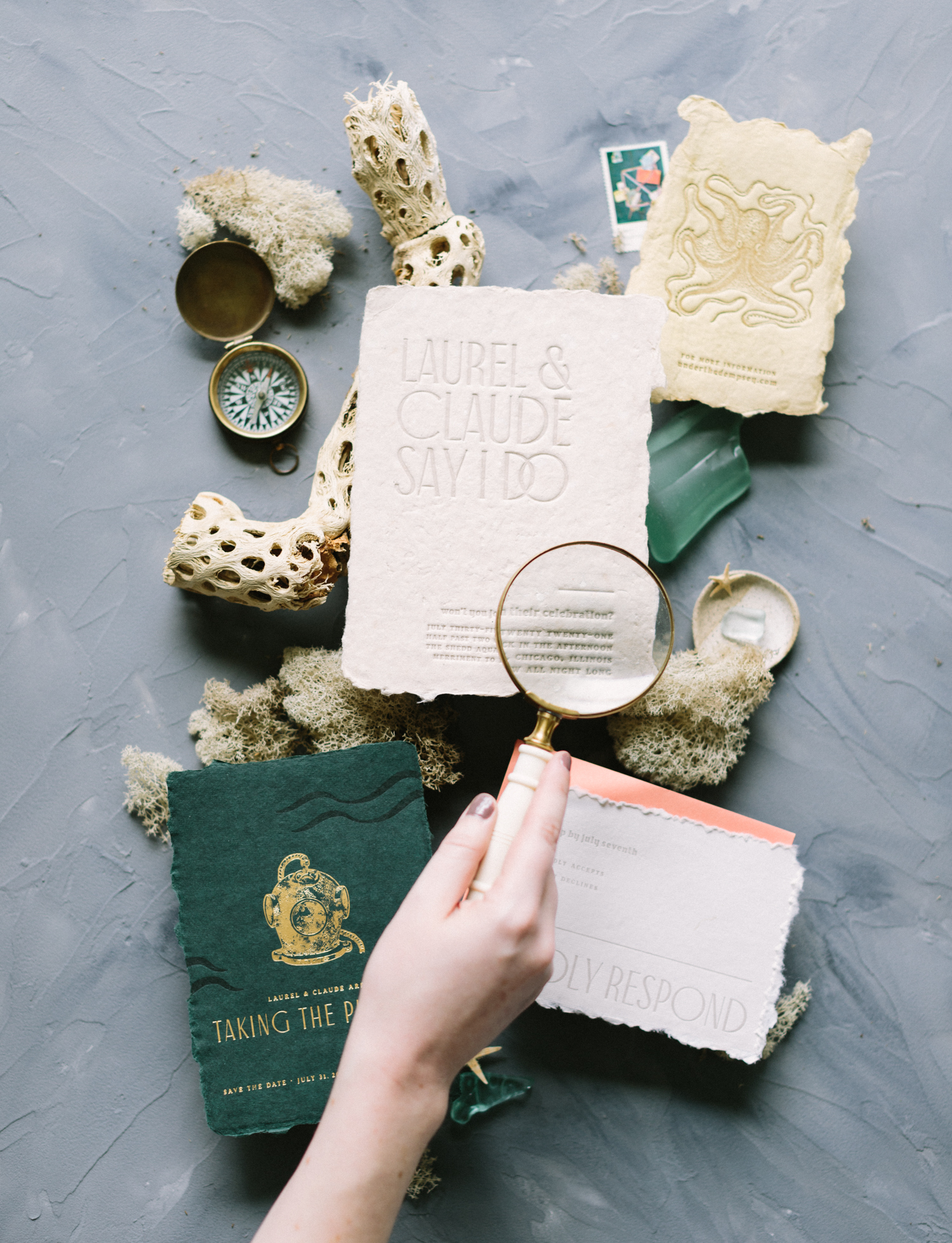 An artist uses a magnifying glass to view a flat lay brand photo of handmade custom letterpress wedding stationery in Brighton, Michigan