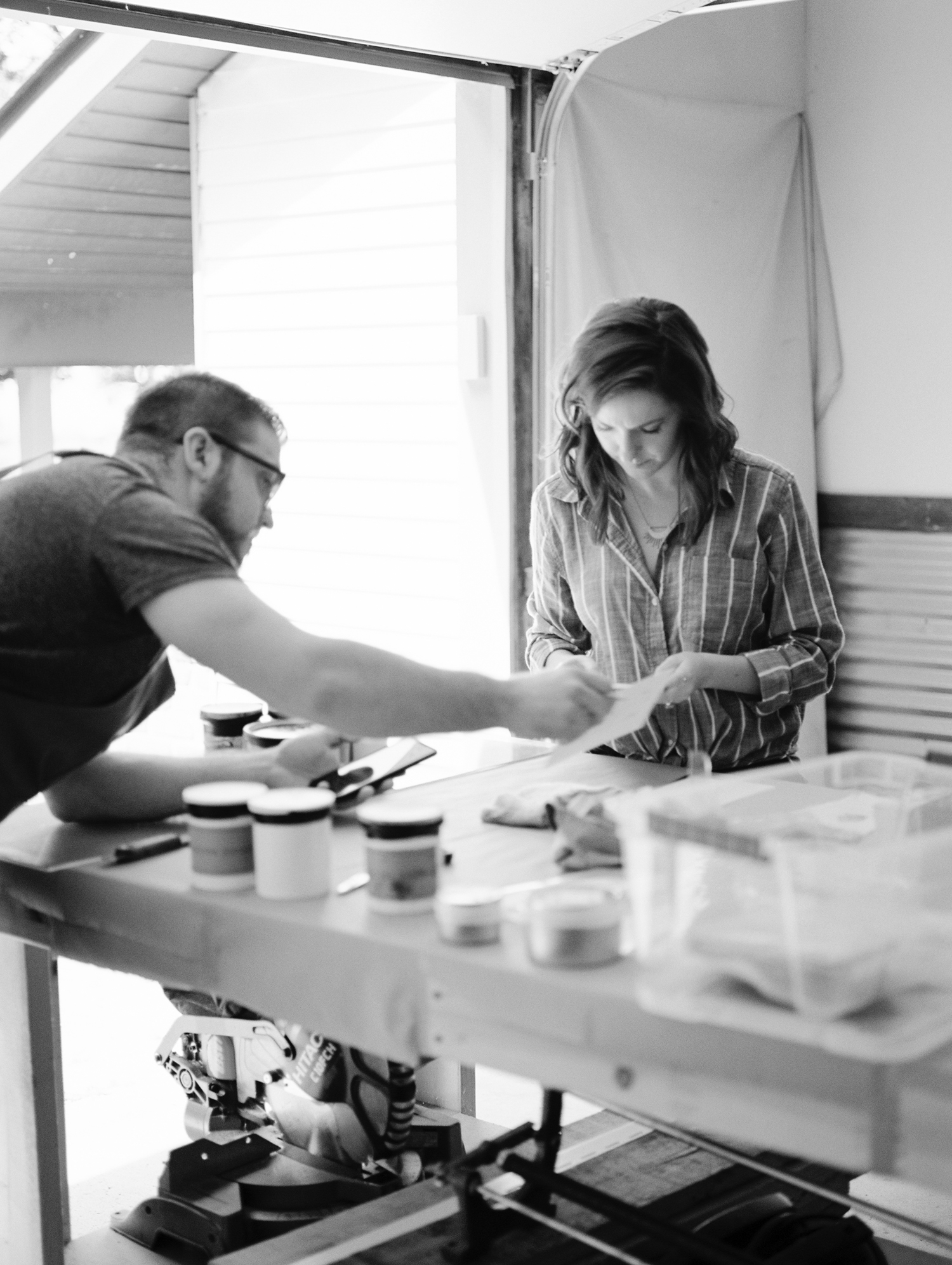 A stationer works with her husband in their letterpress studio during brand photos in Michigan