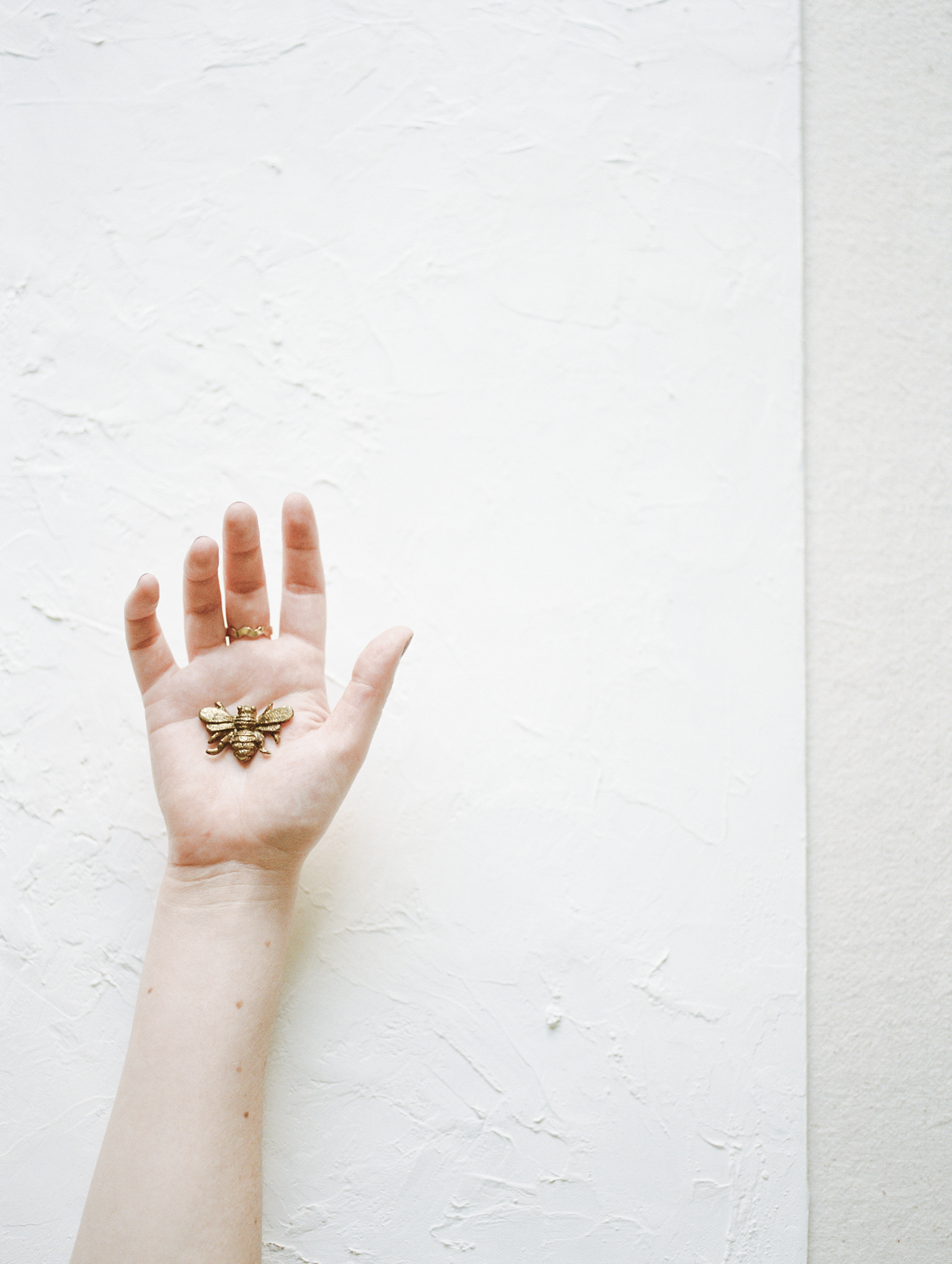 a woman's hand holds a small brass honeybee over a white painterly background