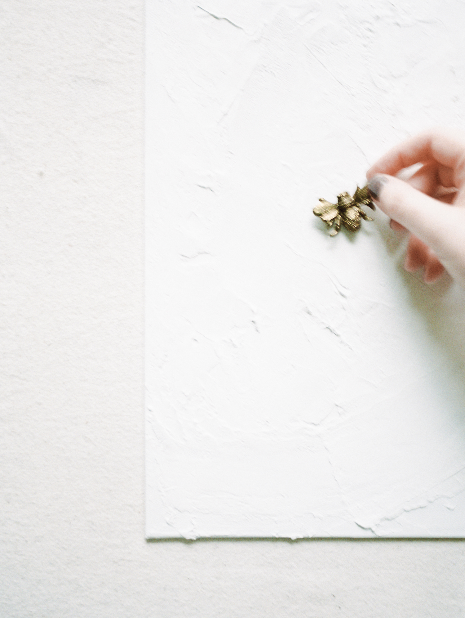 An artist's hand reaches for a small brass honeybee resting atop a white plaster and paint surface during a brand shoot on film in Michigan