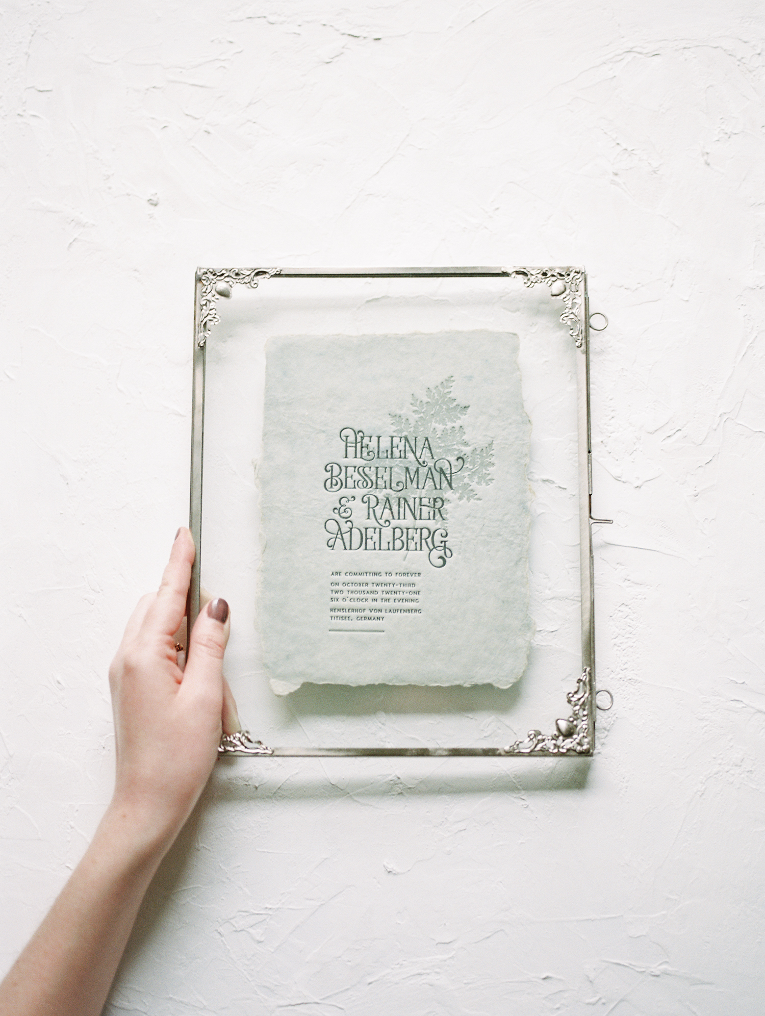 A handmade paper and custom letterpress wedding invitation rests in a glass frame near Detroit, Michigan
