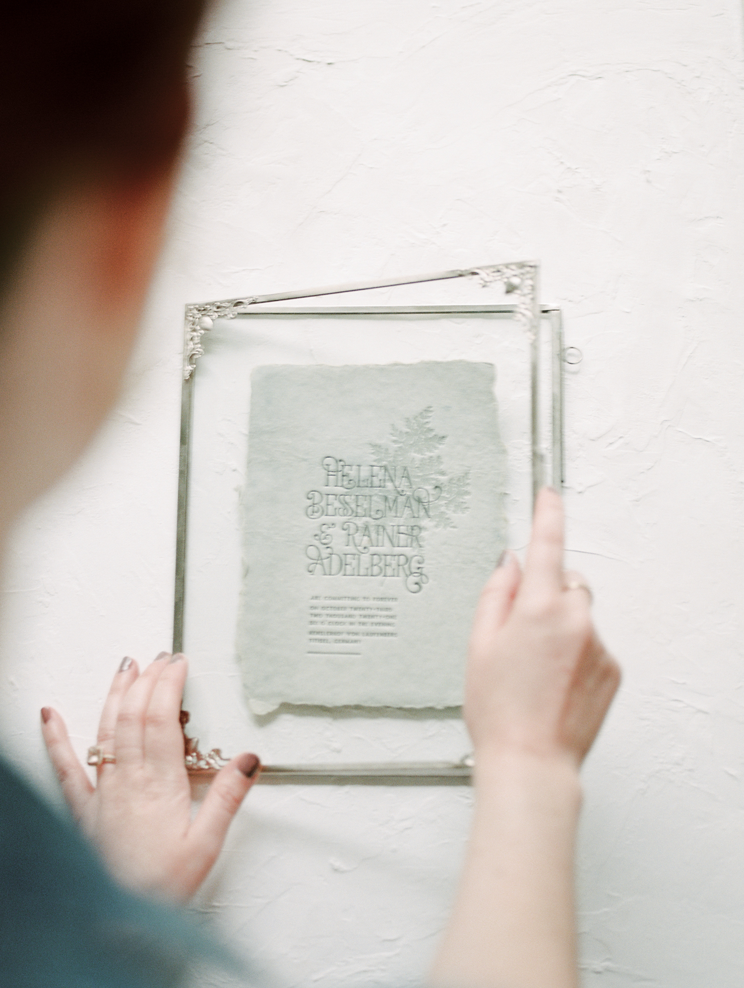 A designer places a handmade paper wedding invitation in a frame near Detroit, Michigan