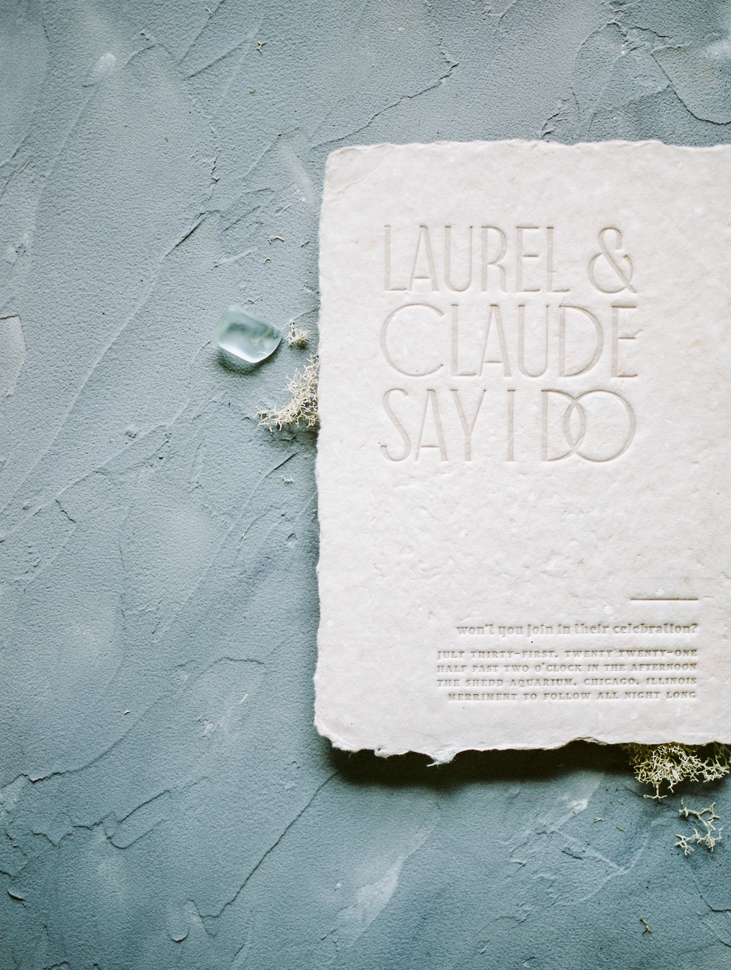 A handmade blush paper wedding invitation with custom letterpress rests on a painterly background in Michigan