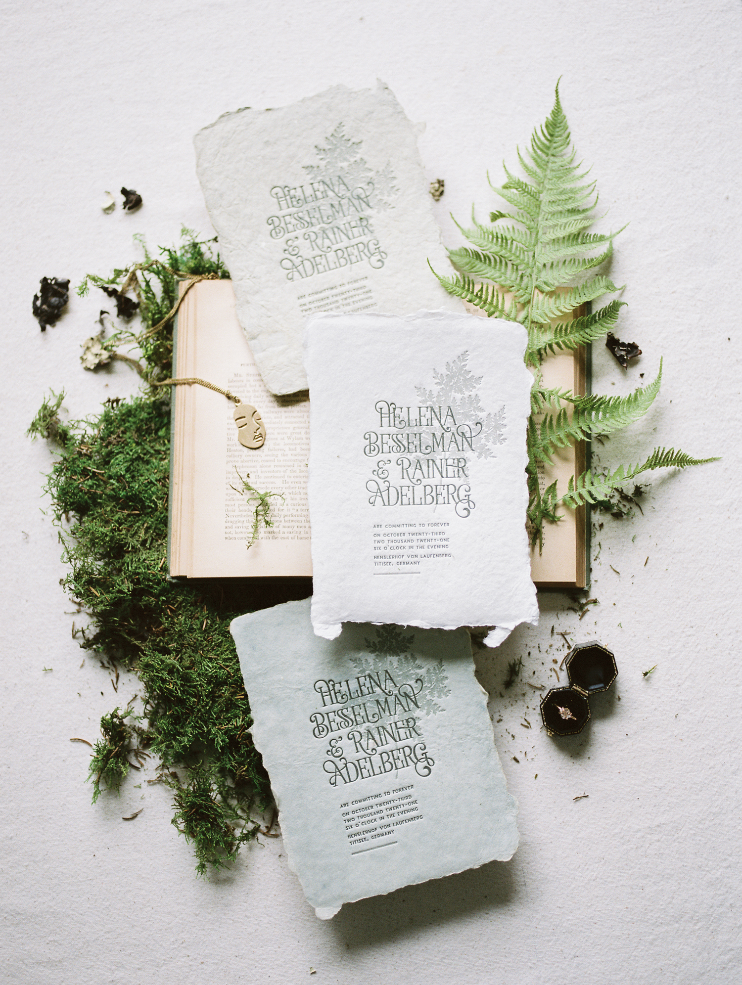 Woodland inspired custom wedding stationery on handmade paper is shown laying atop an antique book with moss and ferns in Detroit, Michigan