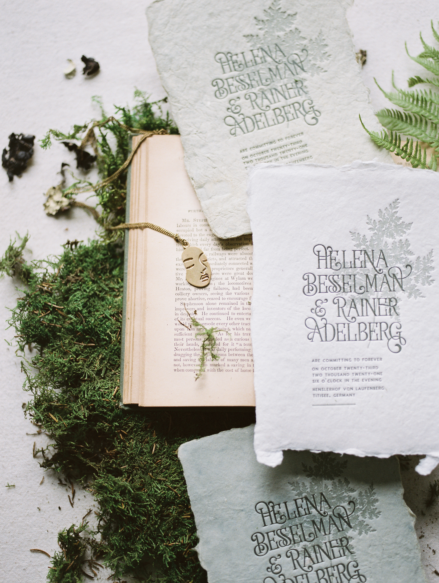 Handmade custom wedding stationery on handmade paper created by a Detroit artist rests next to a brass necklace