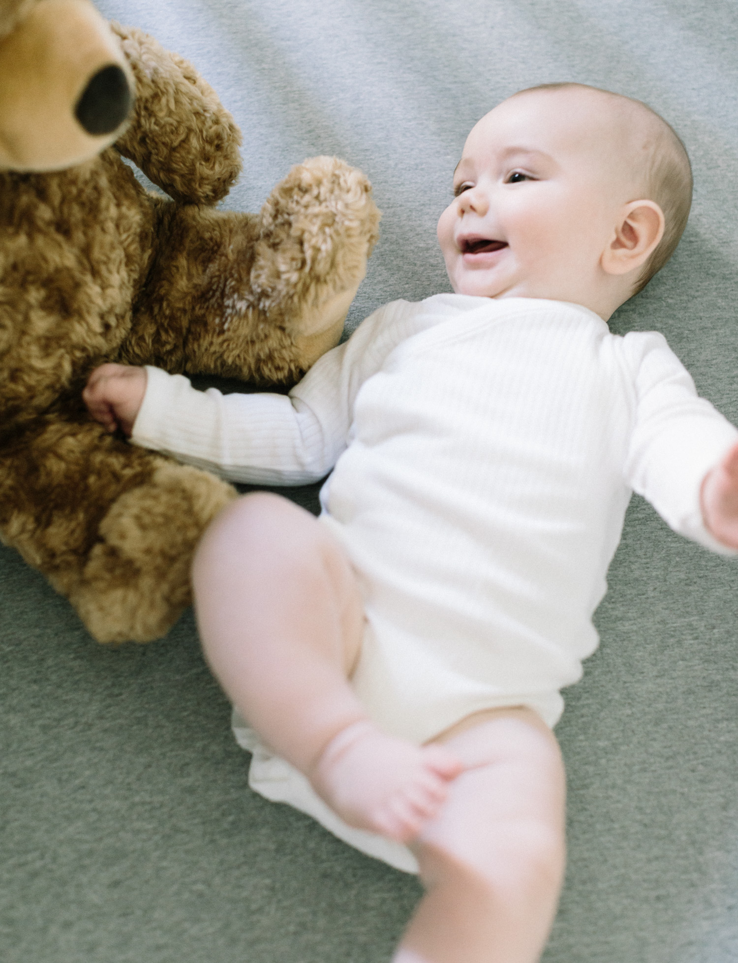A baby boy smiles next to a stuffed bear during family photos at home in Lansing, Michigan