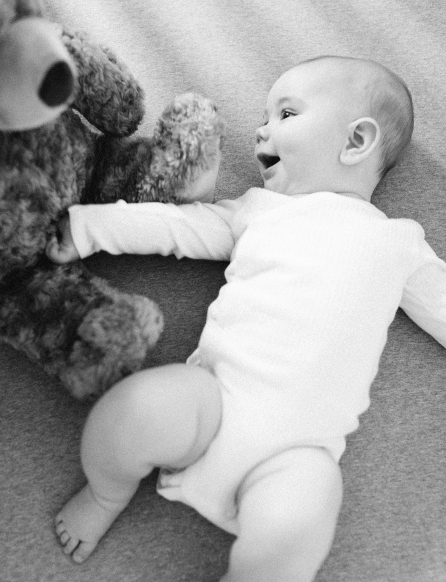 a baby boy plays with a stuffed bear during family photos on film in Lansing, Michigan