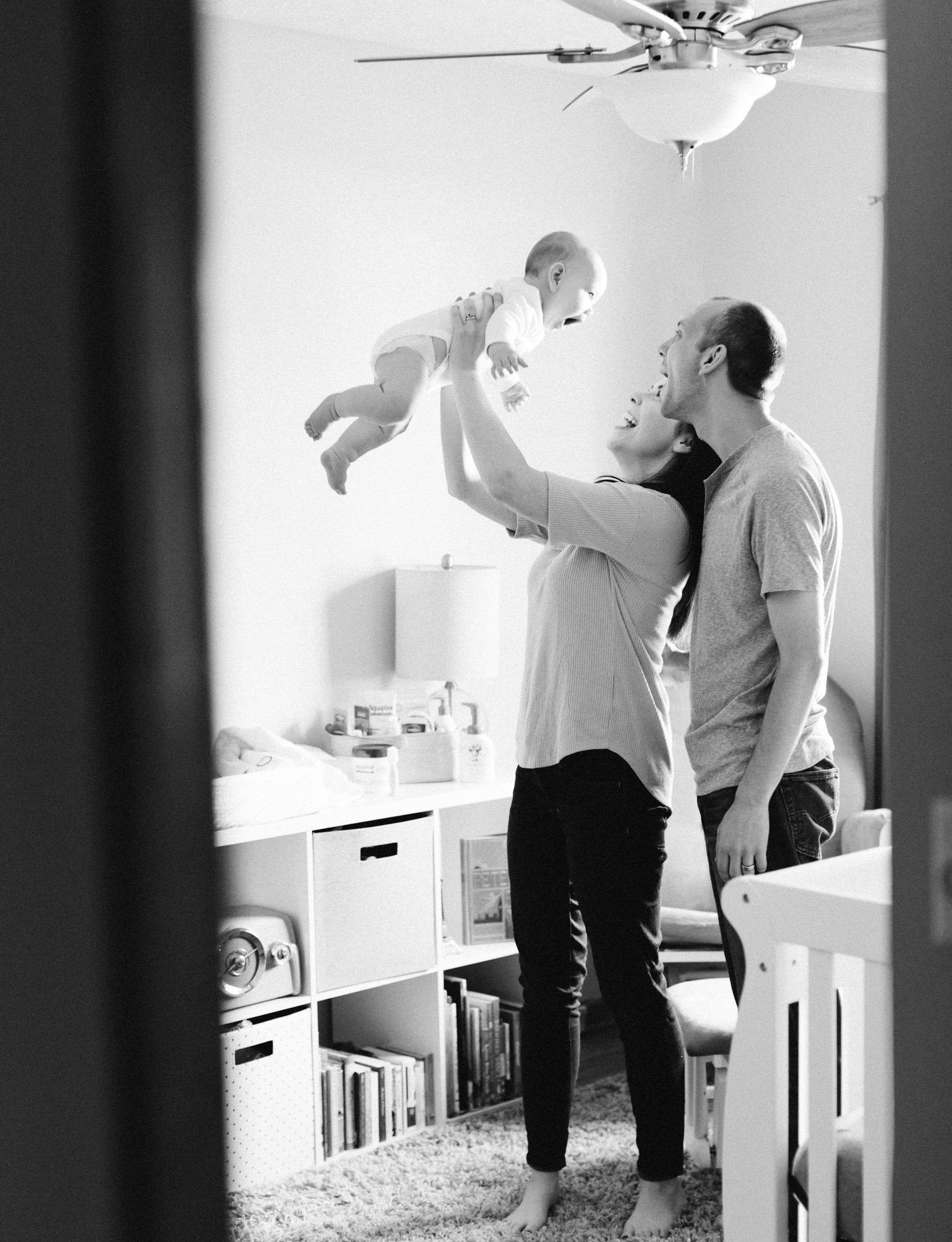 A mom playfully lifts her baby boy into the air in his nursery in their Lansing, Michigan home