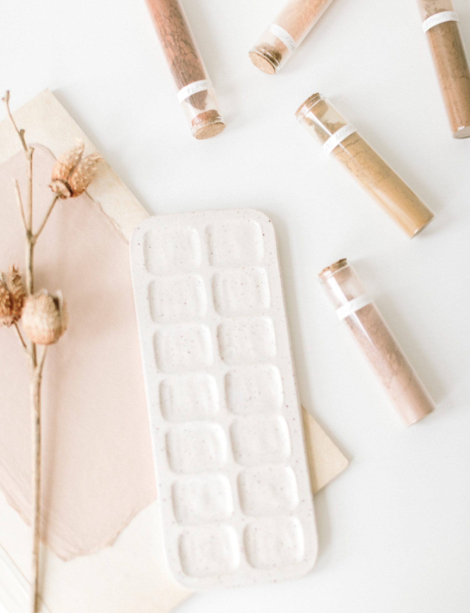 A ceramic paint palette rests on a white surface with paint pigment powder and dried florals for a brand photoshoot in Detroit, Michigan