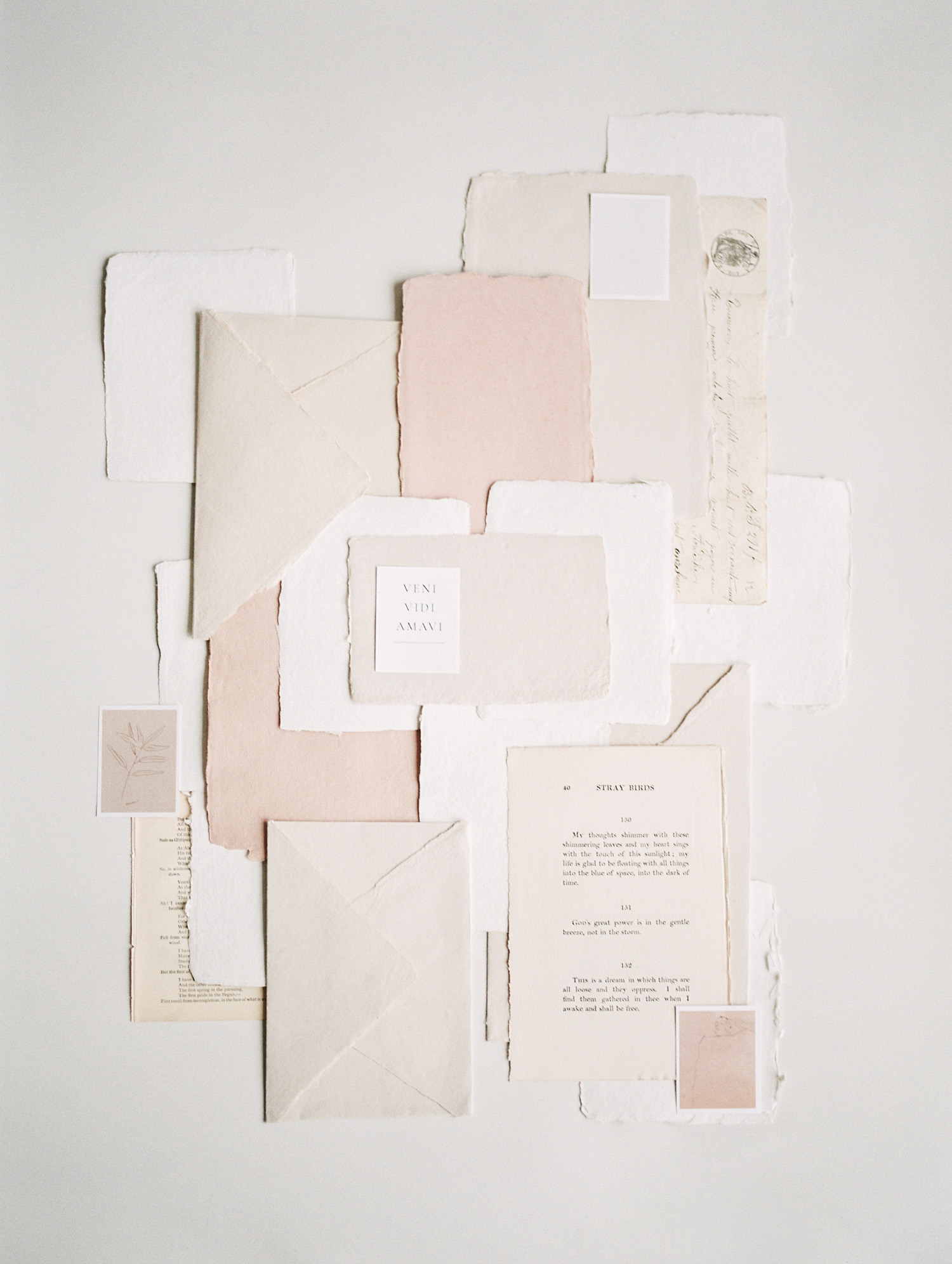 handmade paper and envelopes in warm tones mingle with antique book pages during a brand photoshoot in Michigan