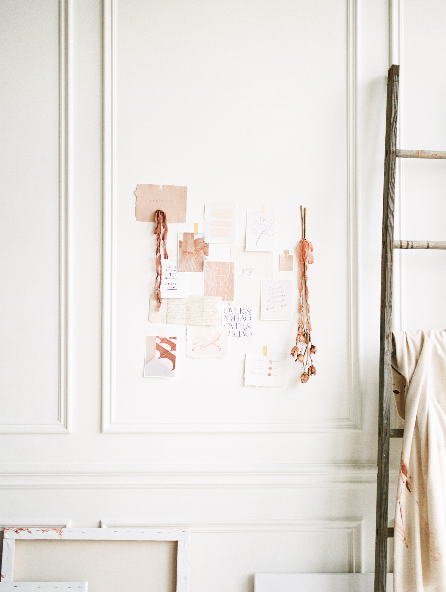 tangible inspiration with warm tones is pinned to a white art studio wall with picture frame molding at Tribe Detroit