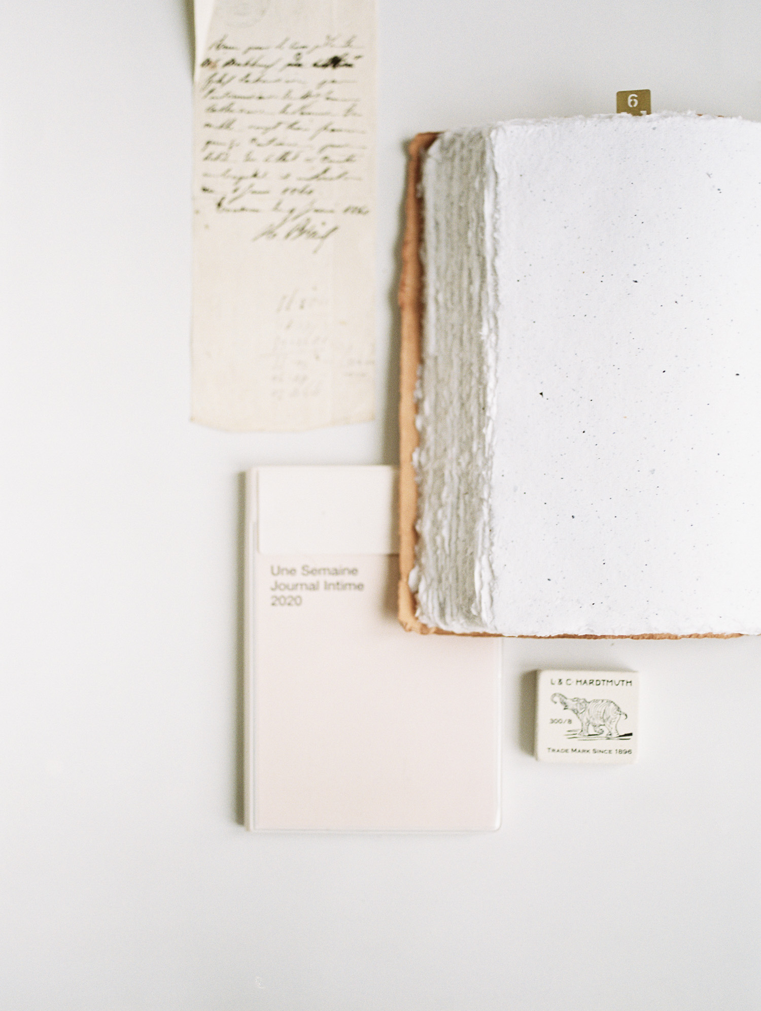a book of speckled handmade paper is layered on top of a journal and an antique handwritten letter at Tribe Detroit