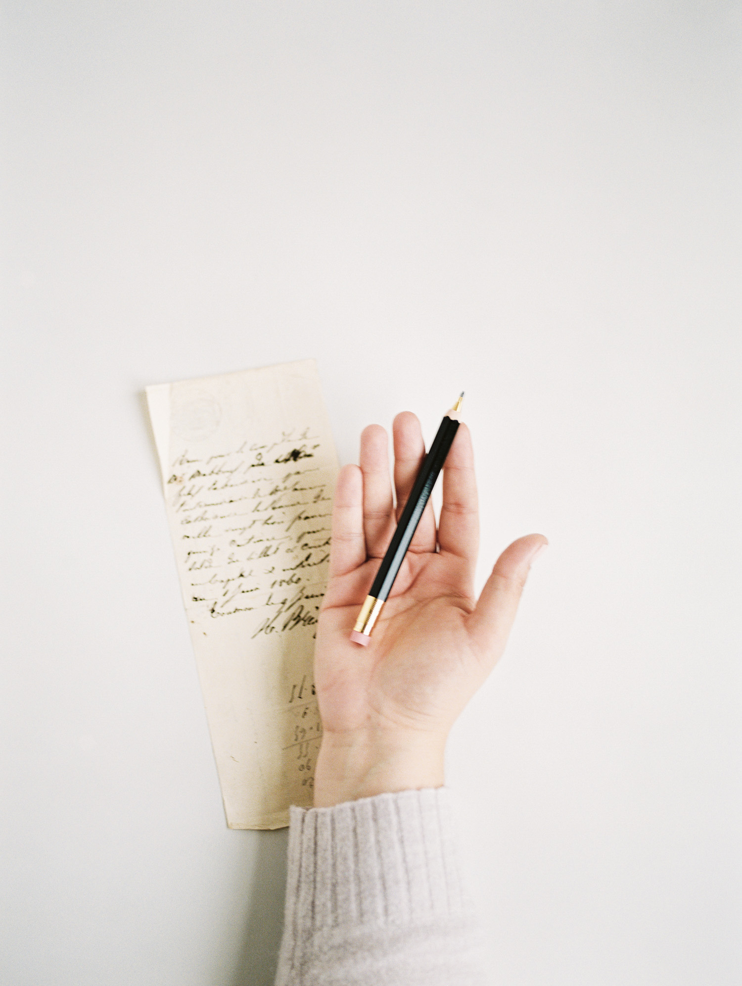 a pencil rests in an open hand next to an antique handwritten note during a brand photoshoot in Michigan