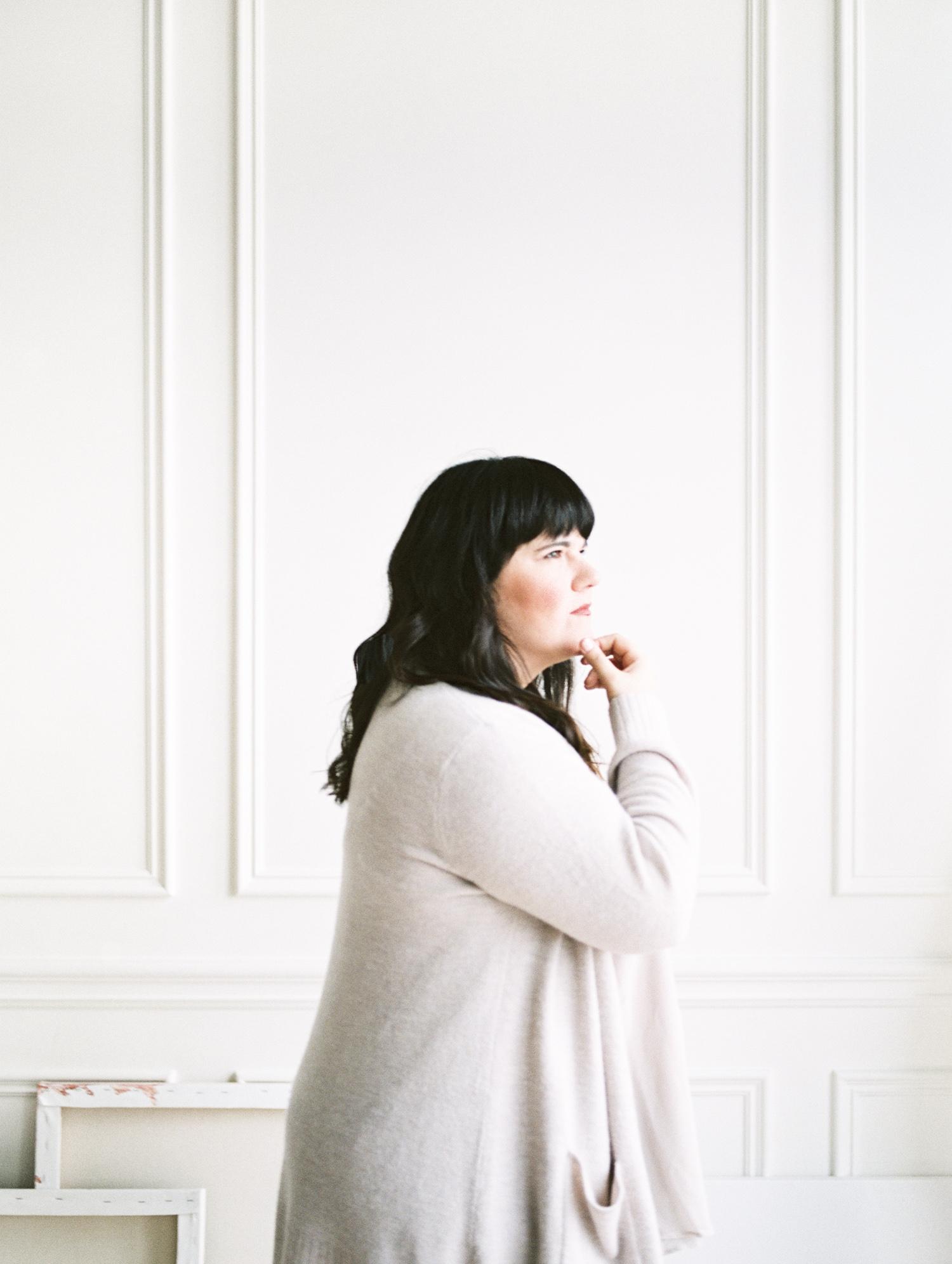 A fine art brand headshot of a female creative during an artist brand photoshoot in a white studio in Detroit, Michigan