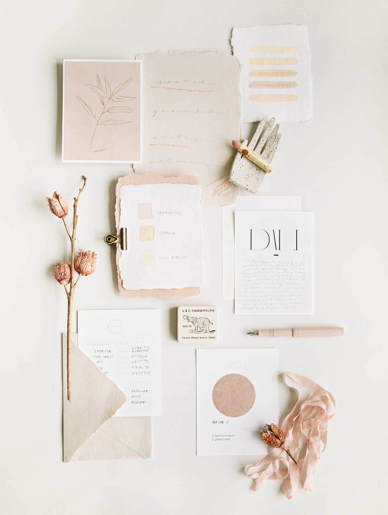 a flat lay with warm toned handmade paper, dried floral, and painterly artwork captured for the Artist Website Academy in Detroit, Michigan