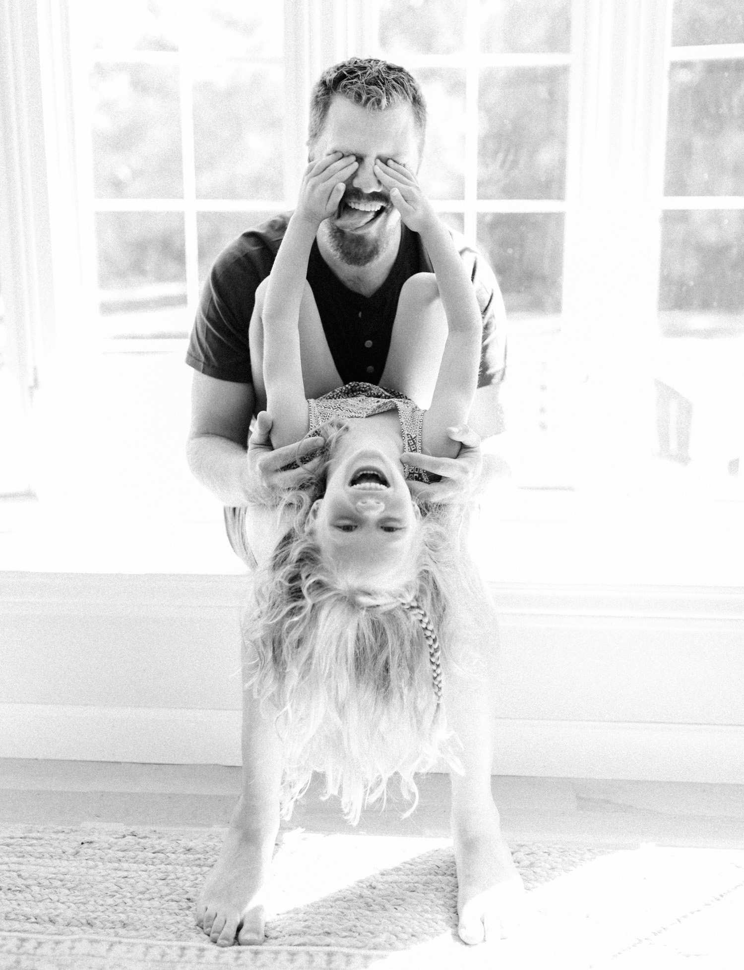 A father plays and laughs with his daughter while she covers his eyes during their natural lifestyle family photos at home near Lansing, Michigan