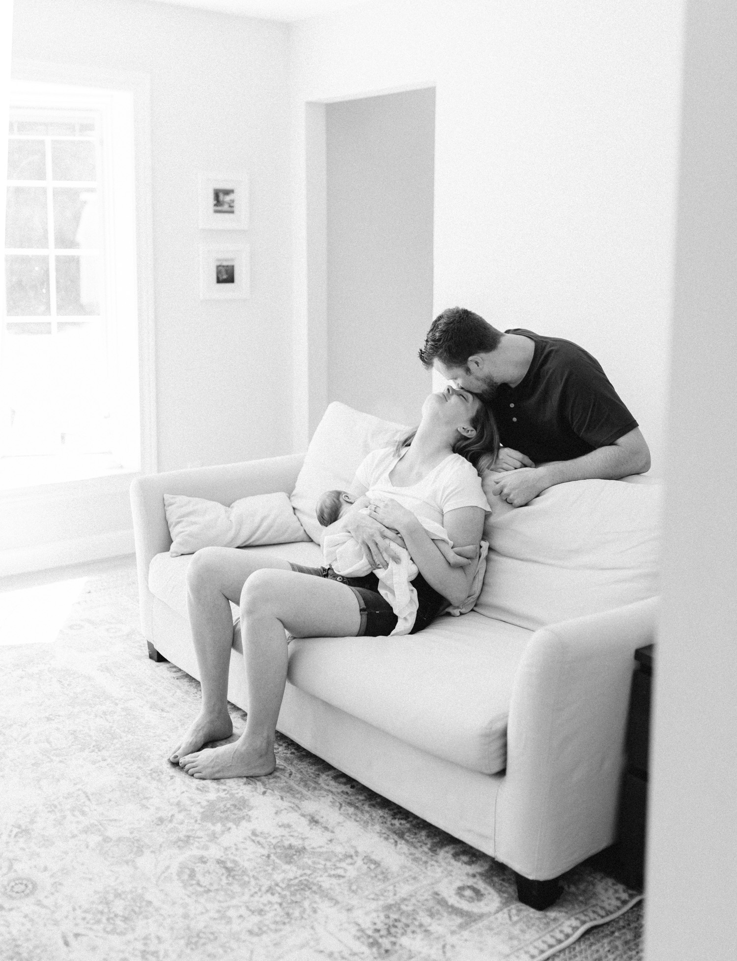 A woman is kissed by her husband while she feeds their newborn baby at home during natural family photos in Michigan