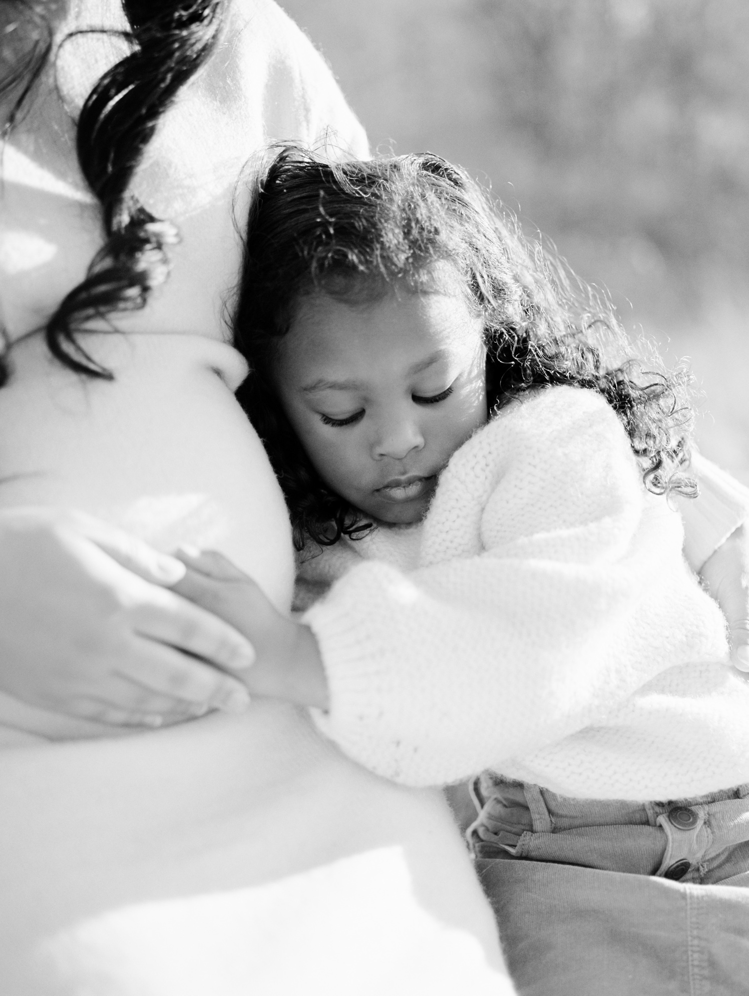 A little girl quietly hugs her mother's pregnant belly during a mother-daughter maternity photoshoot on film in Michigan