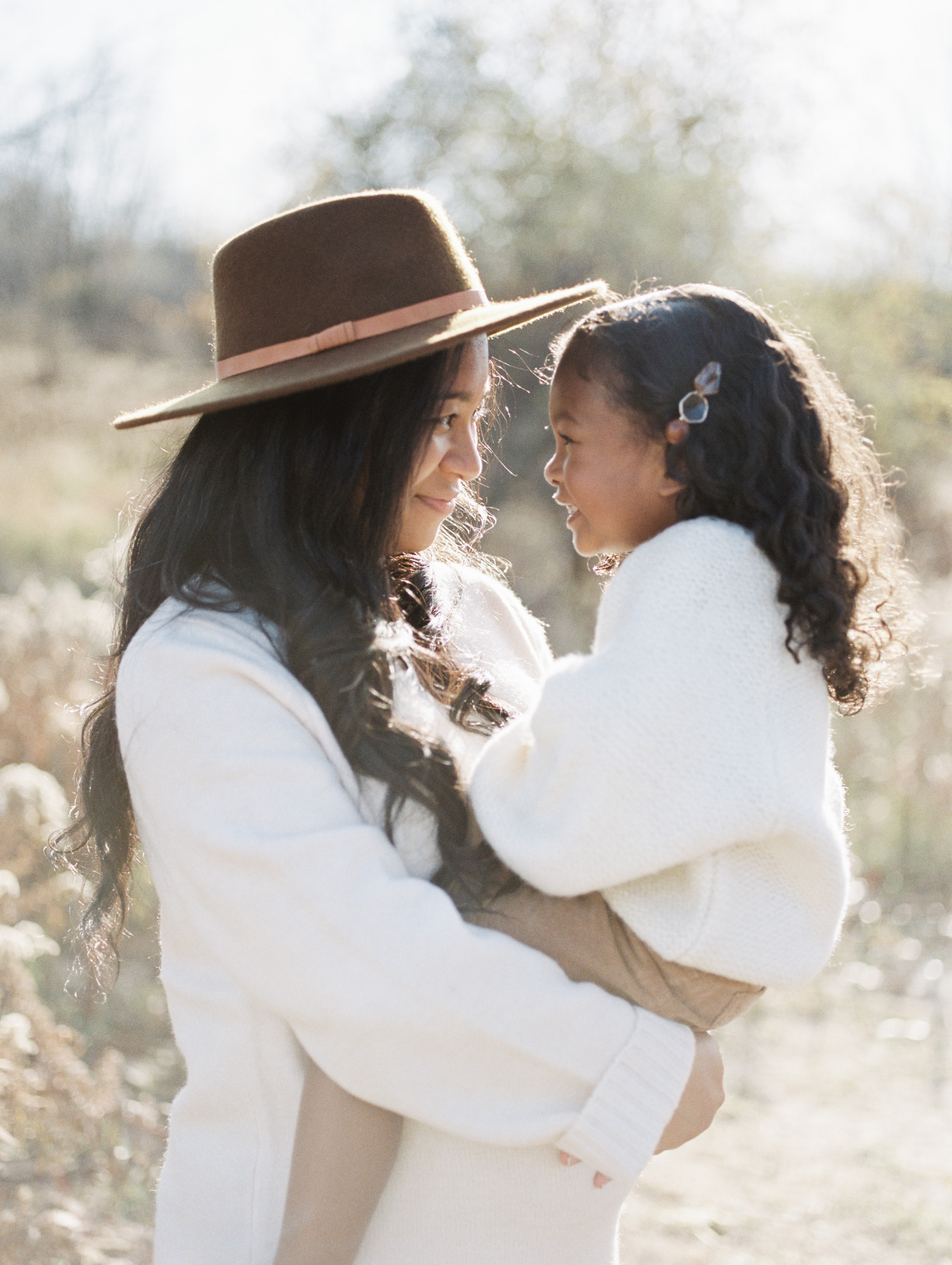 A black mother and daughter smile at each other during film maternity and family photos near Detroit, Michigan