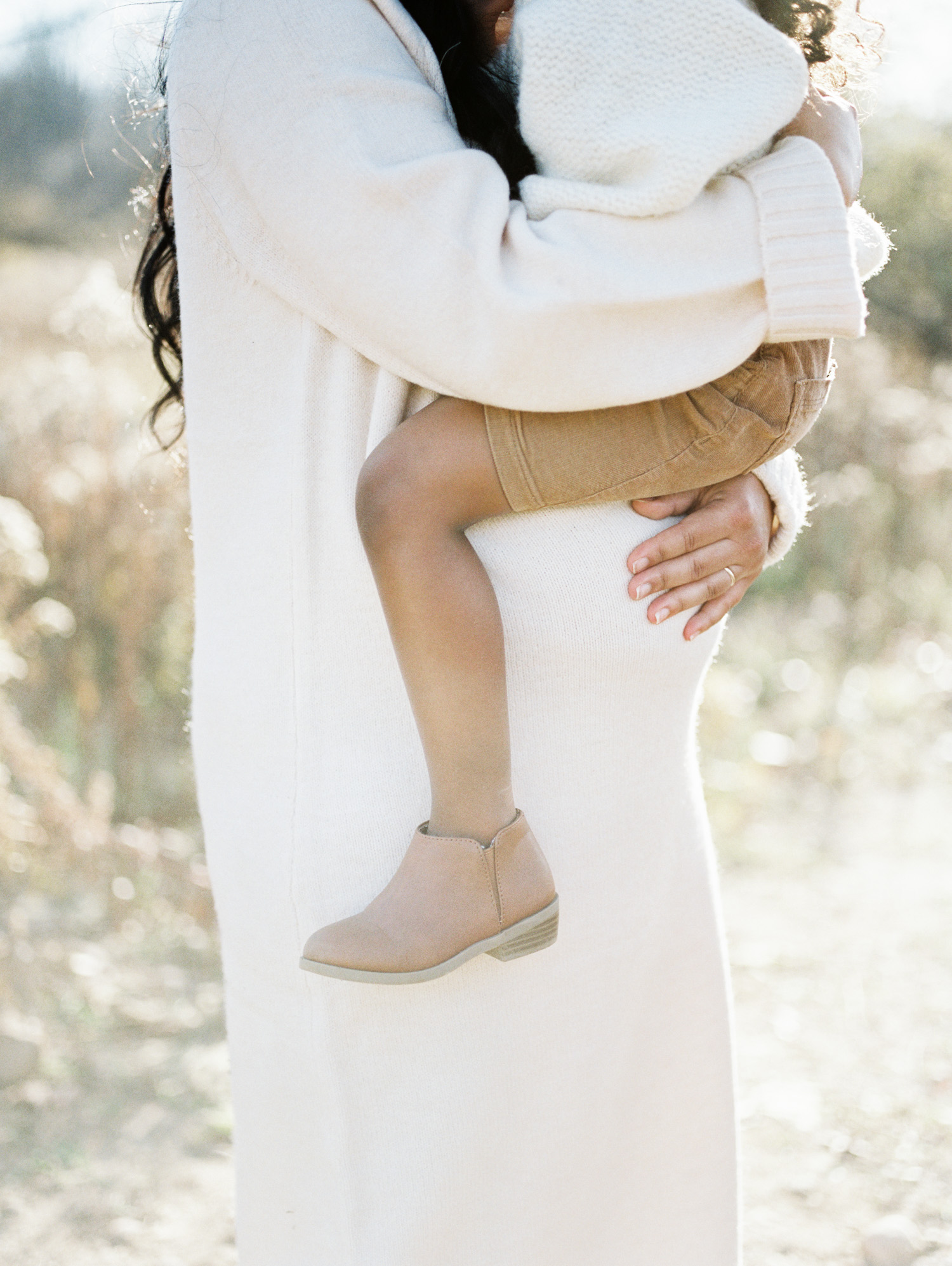 A mother holds her little girl above her pregnant belly, both in neutral outfits for film family and maternity photos near Detroit, Michigan