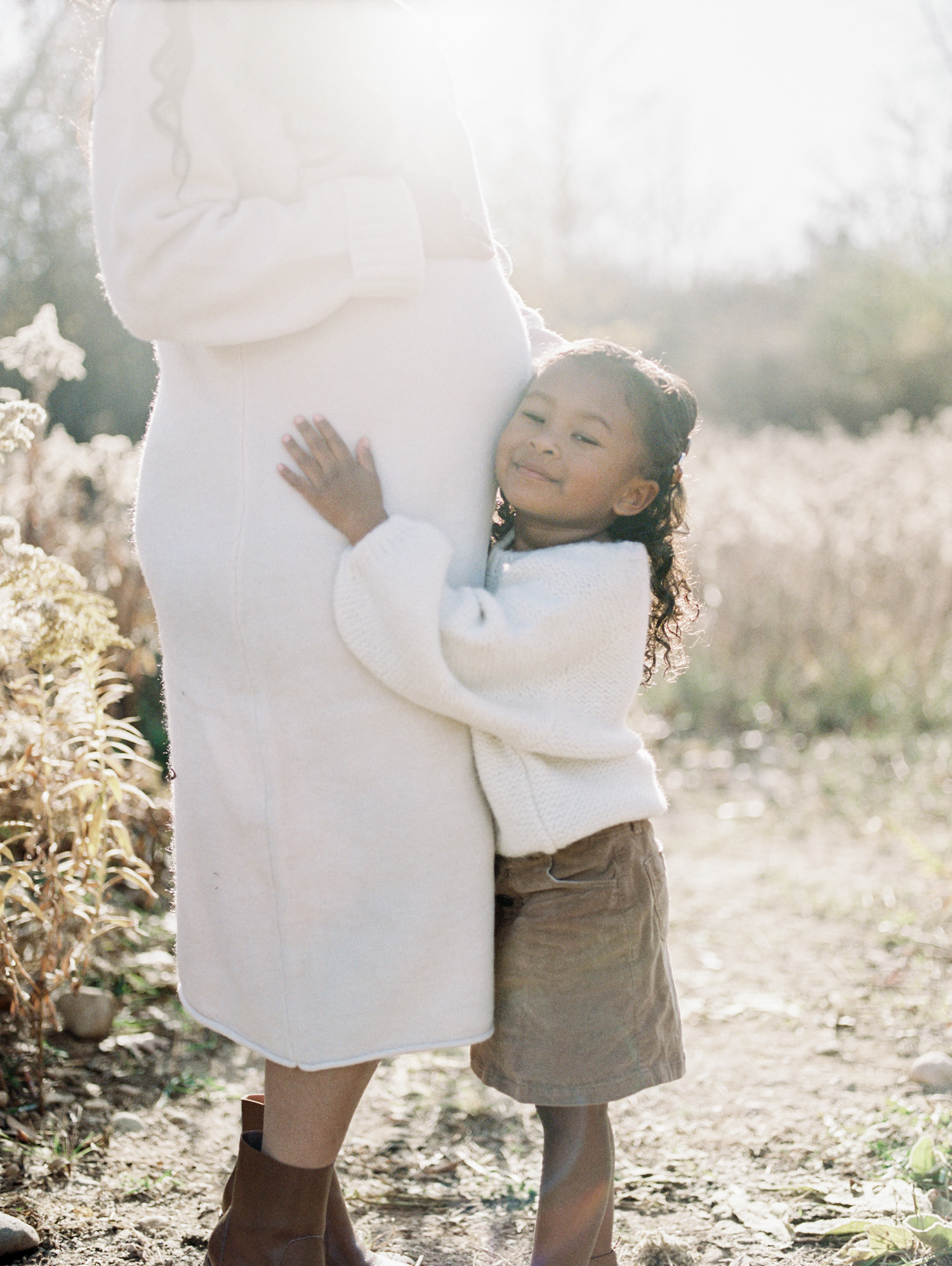 A little girl hugs her mother's pregnant belly during a maternity photoshoot on film near Detroit, Michigan