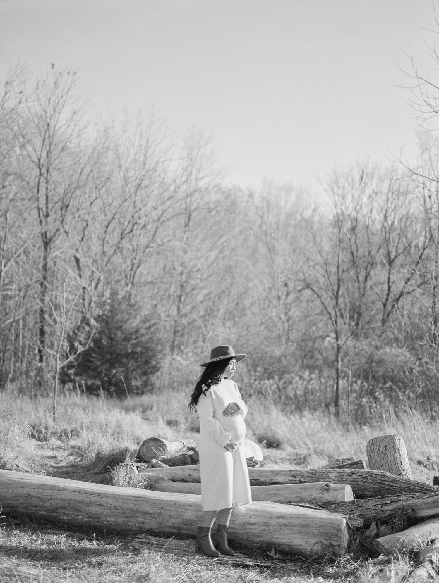 A black mother holds her belly during her maternity shoot captured by a film photographer near Detroit, Michigan