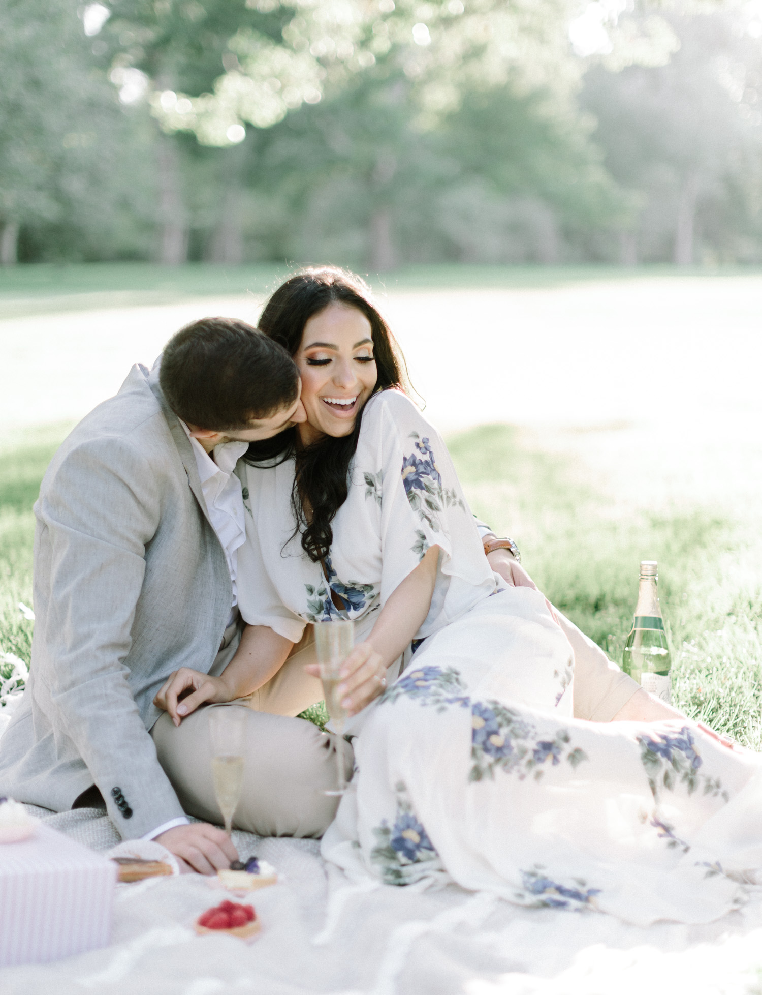 A couple cuddles up during their picnic engagement photos on film at the Ford House