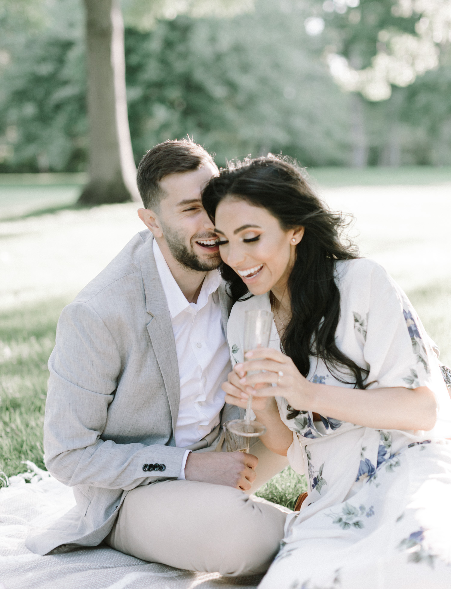 A couple laughs with champagne during their picnic engagement photos on film in Michigan